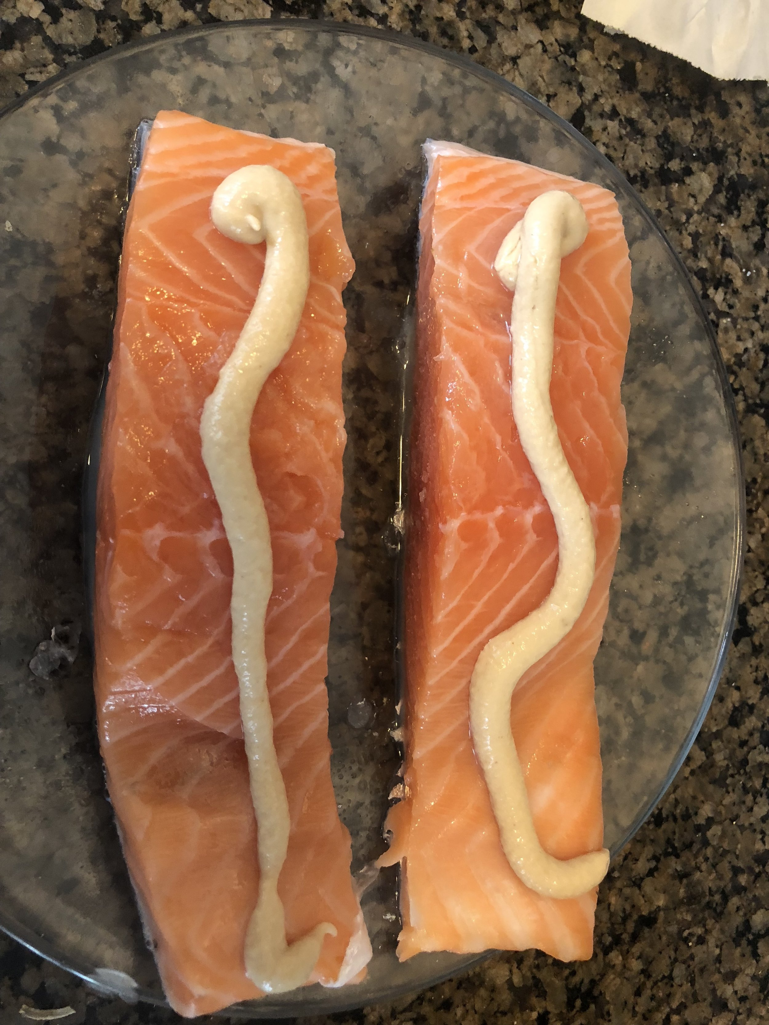 portion your salmon into 2 steaks  spread the mustard on the top of the salmon, season with salt and pepper and then dust with paprika.