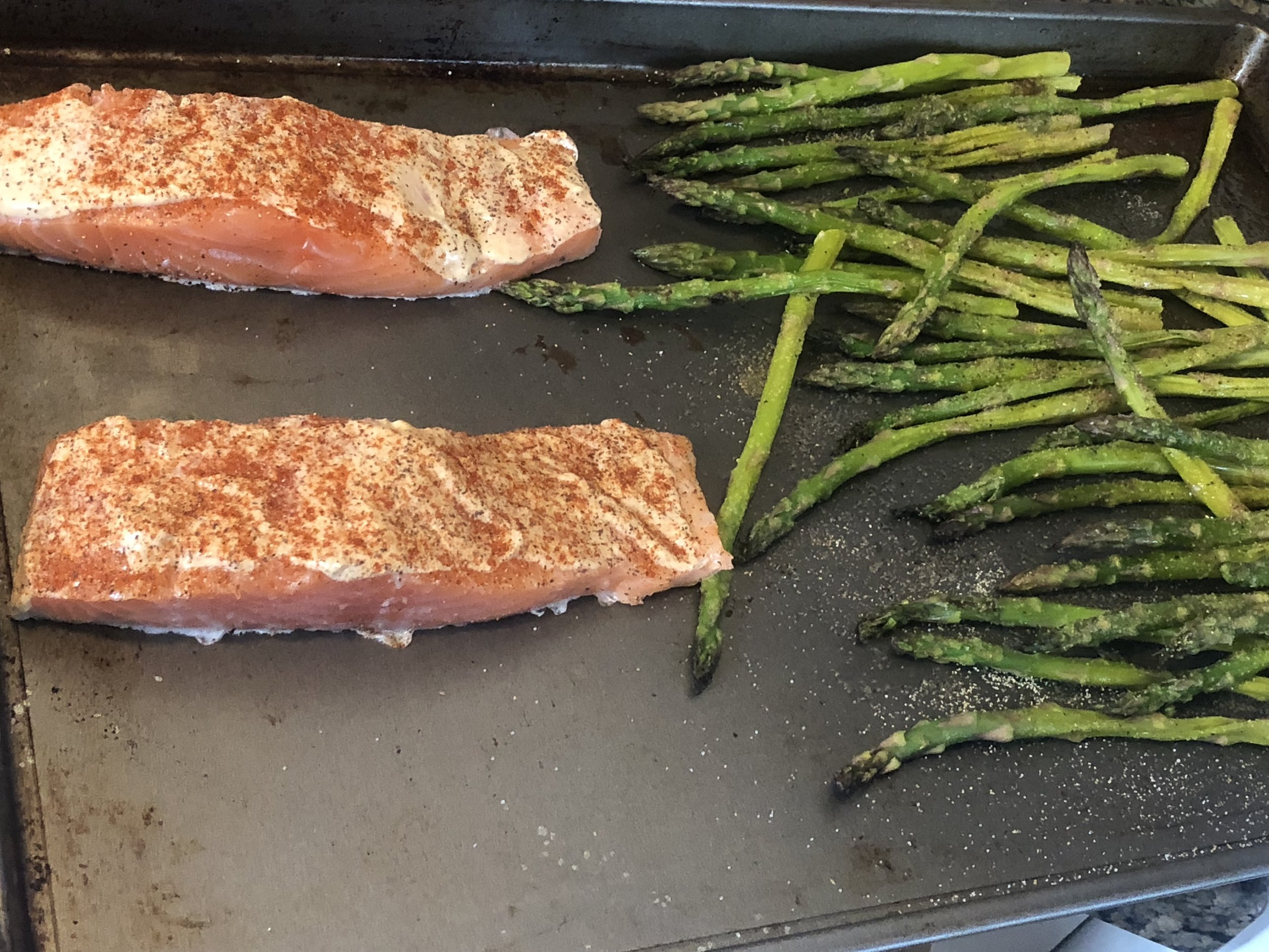 when your kitchen timer has expired, put your salmon onto the pan with the asparagus, skin side down. Cook for 15-20 minutes or until the salmon is cooked through.    My Comments: This recipe included coating the salmon with Panko and I will try this in the future, but I was concerned because the salmon was still frozen in the middle and I thought it would cook more evenly without it.
