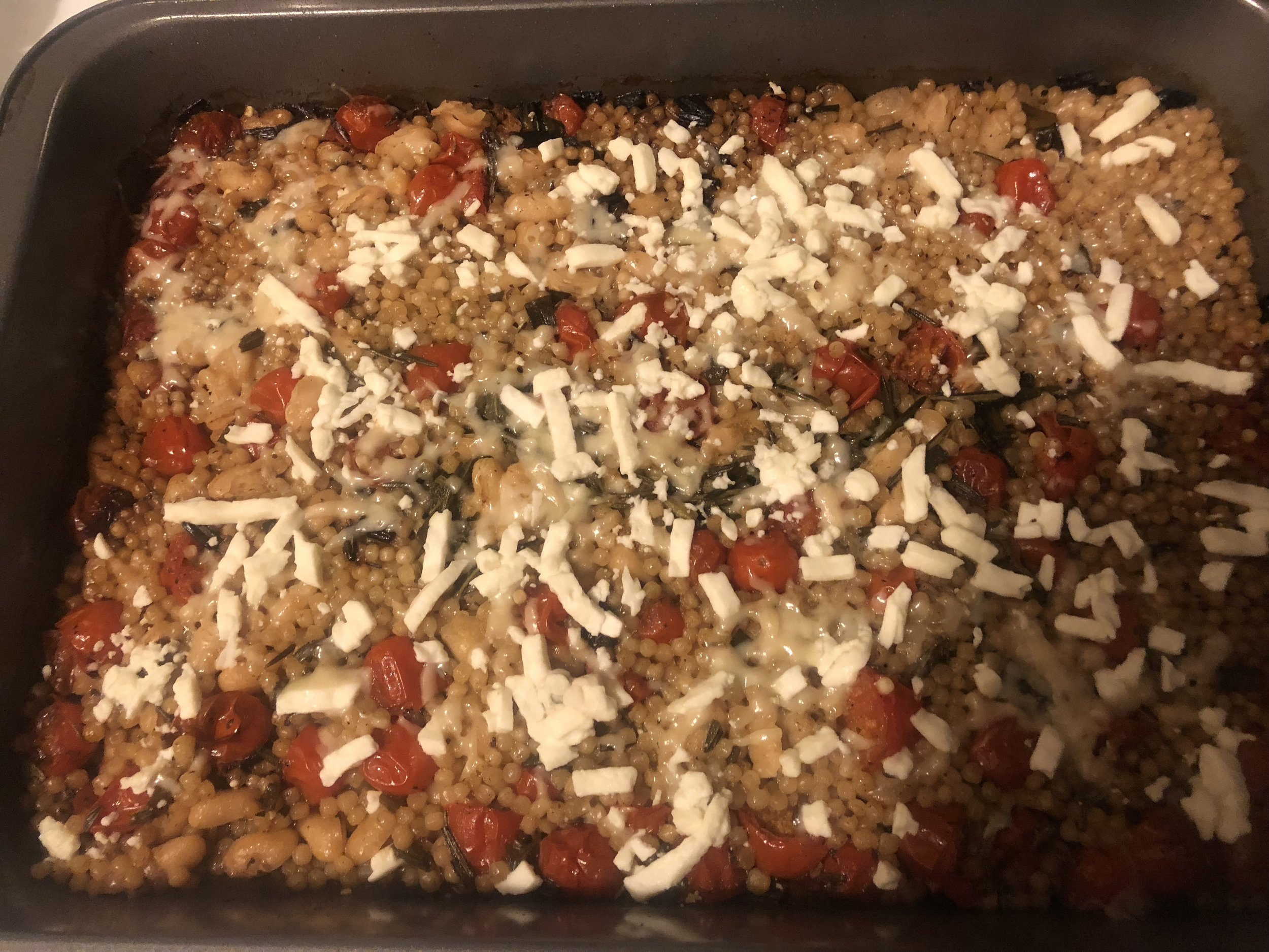 ingredients  Pint of grape tomatoes  cup of feta  0.5 cup of shredded parmesan  3 sprigs of oregano  bunch of scallions  2 tsp of balsamic vinegar  1.5 cup of pearl couscous  2 cups of chicken broth  salt and pepper  tsp of cumin  can of cannelloni beans  2-3 medium/massive cloves of garlic  5-6 tsp of olive oil