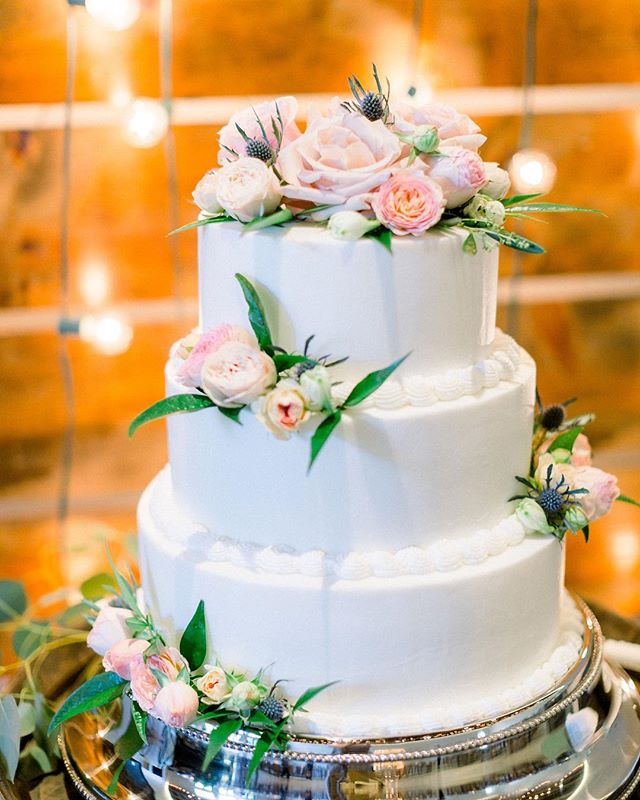 Love that this cake was created by the cousin of the groom and adorned with fresh flowers from Two Shall Become One Flowers, but my favorite part? That rustic backdrop with bistro lights... swoon. 😍 . . . Venue: @pageofarms Photography: @jodyatkinsonphoto Planner: @cerasingleyevents Florist: Two Shall Become One, Fatima Bettencourt Dress Shop: @kleinfeldbridal Dress Designer: @pninatornai Bridesmaids: @bellabridesmaids Veil: @kleinfeldbridal Hair: Jessica Vaz Makeup: @makeupbymarkelle Suits: @menswearhouse Rings: @geigersfinejewelry Caterer: @big_vics_bbq DJ: @djbobbysanchezPhoto  Booth: @pennyandco.rentals  Style mat: @jrd_artshop #soontobesilva
