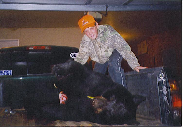 derek holding up front shoulder of bear in truck.jpg