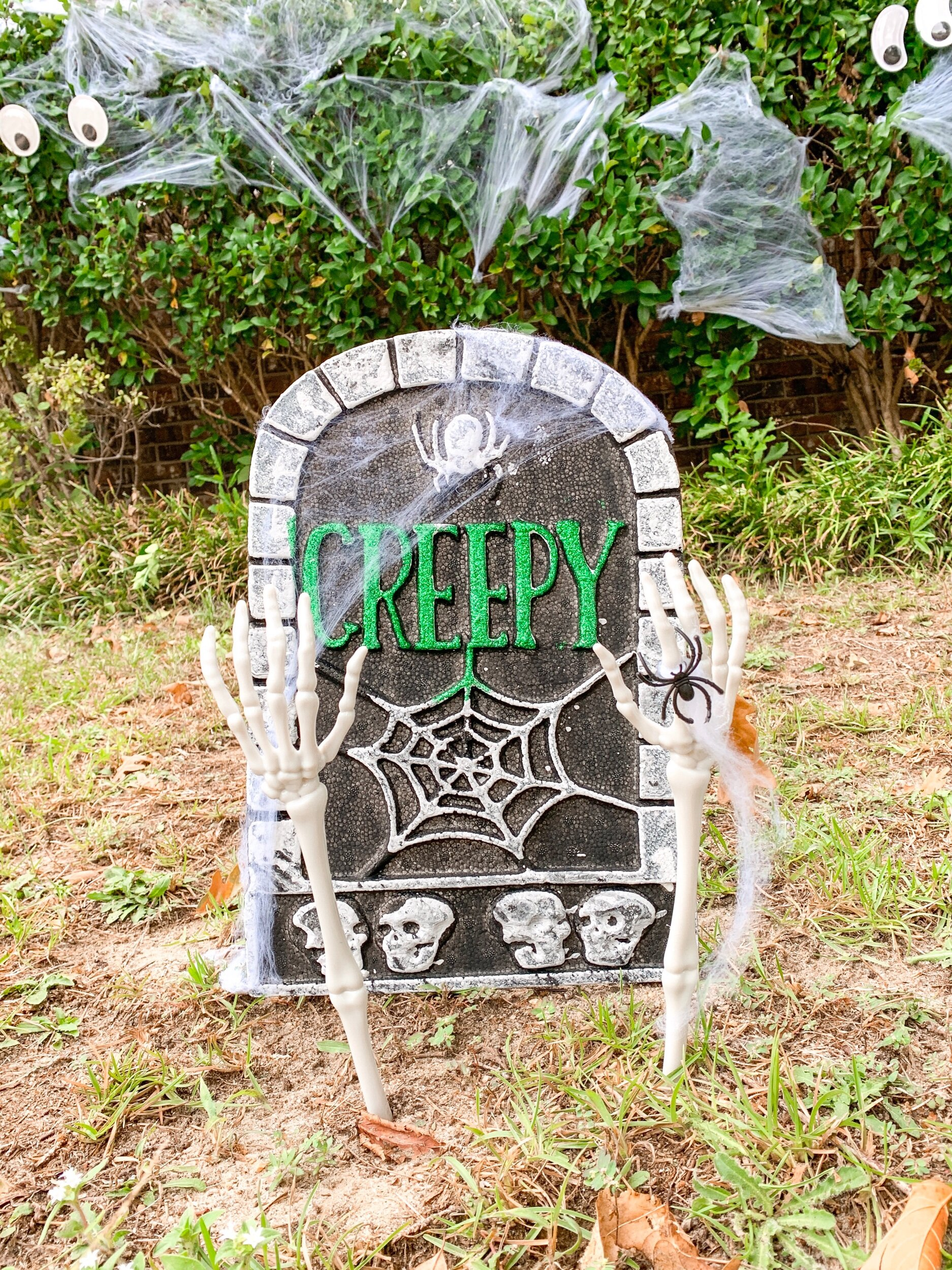 My favorite easy affordable Halloween decoration from the Dollar Tree!! $1 styrofoam gravestone , $1 skeleton arms (actually tongs), $1 spider webbing with spiders. $3 is NOT a bad deal.