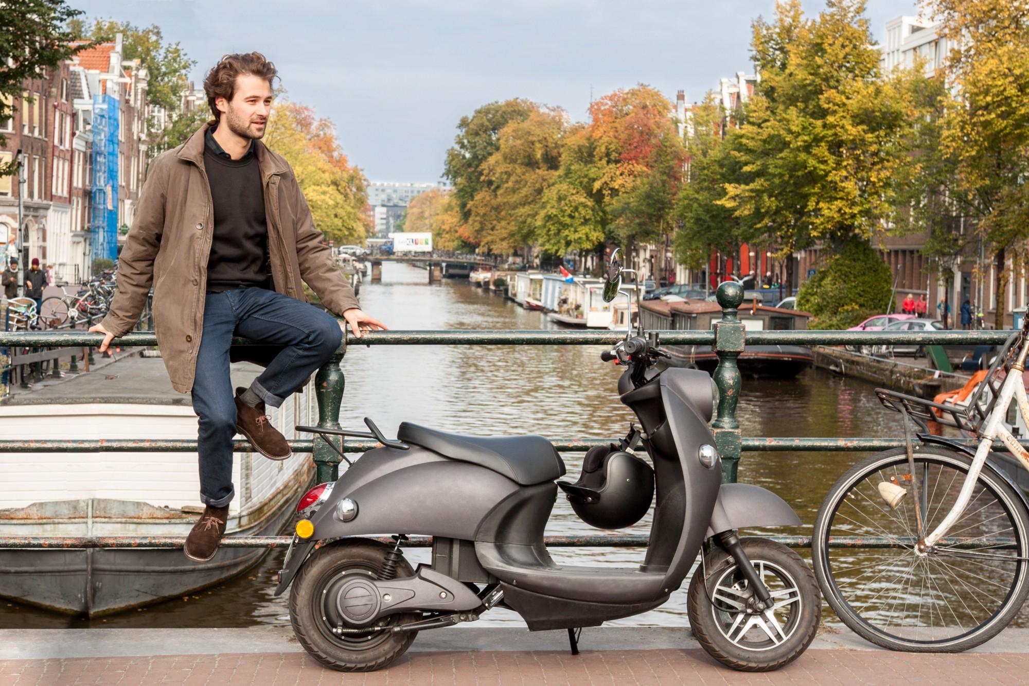 Ein 3000 Watt  unu-Eektroroller  in Midnight Black parkt an der Gracht in Jordaan, Amsterdam.