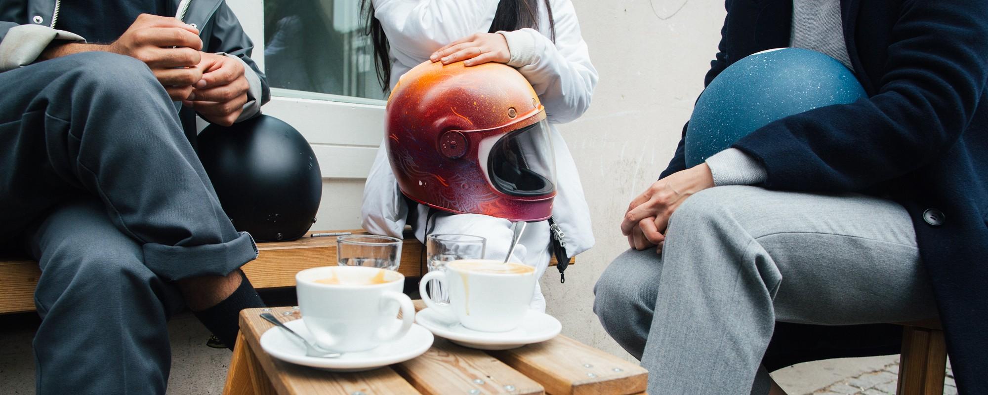 Vrienden die net van de elektrische scooter zijn afgestapt om met hun motorhelmen koffie te gaan drinken.