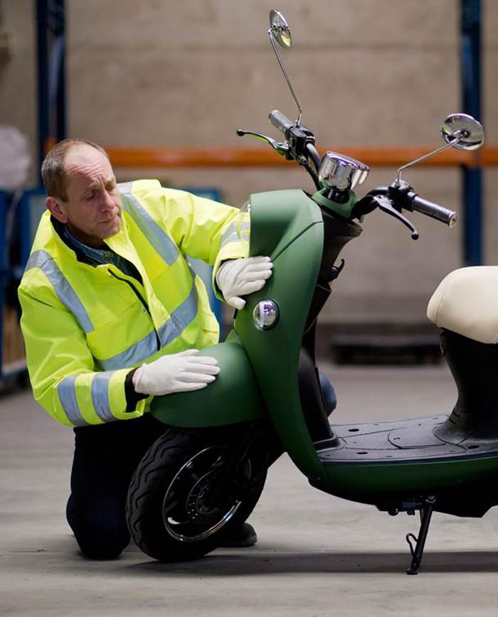 Man die een unu scooter controleert op foutjes