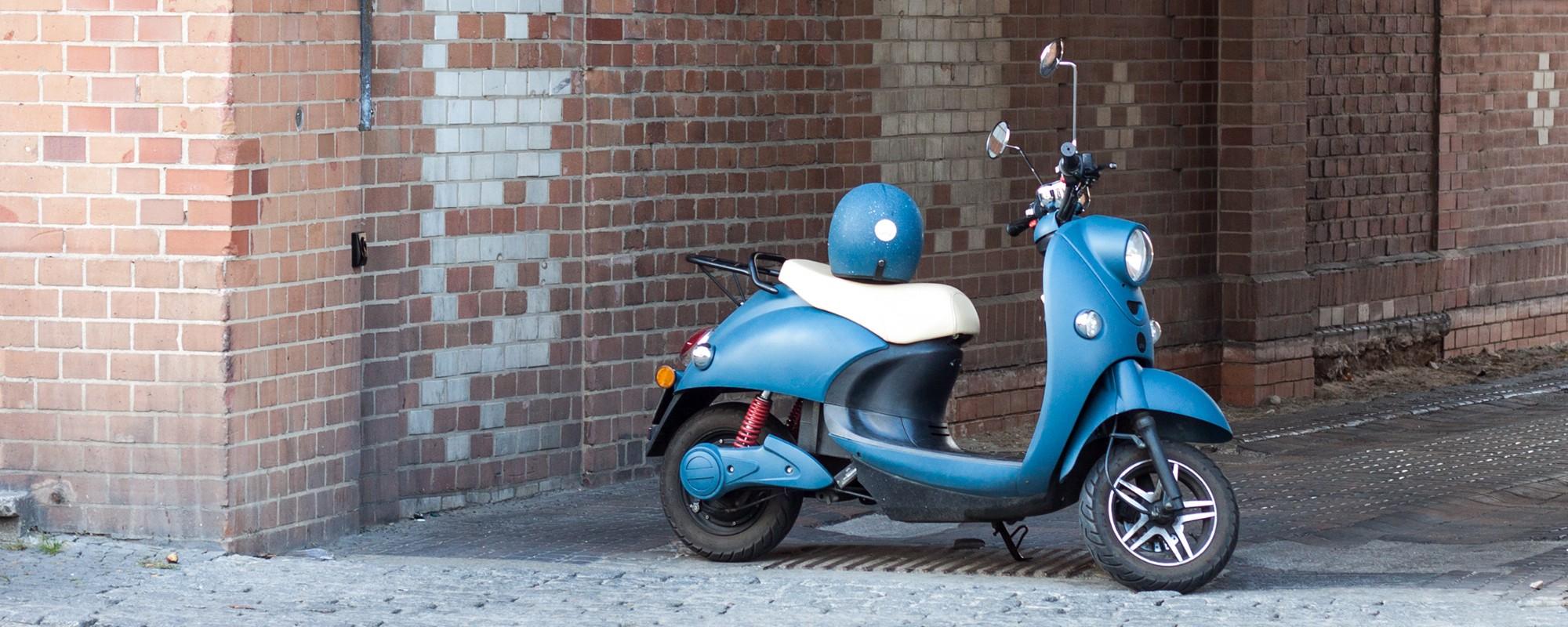 Lichtblauwe unu scooter met op de achtergrond een muurtje