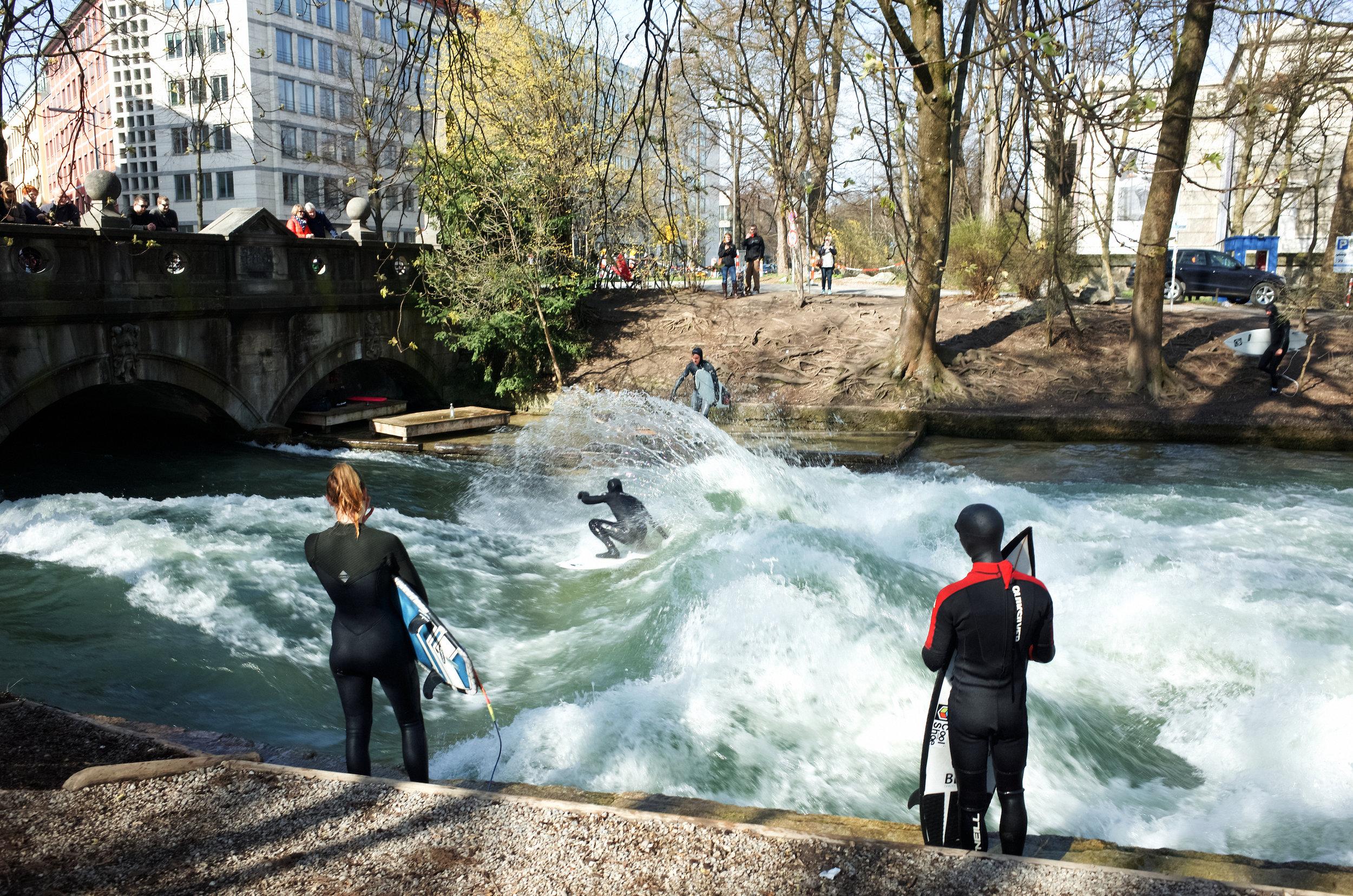 Halt am berühmten Eisbach, der durch den Englischen Garten fließt. Er ist berühmt für seine künstliche Welle, die Surfer aus allen Regionen anlockt, um dem Wasser zu trotzen.