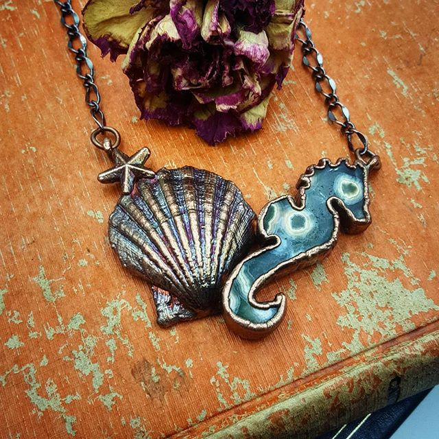 (Update: SOLD) A relatively calm, and mild-mannered creature, the #seahorse is seemingly content to roam the seas. Their bodies are geared for ambling-type motion – not for speed. Thus, they are symbolic of patience and contentment – they are happy with being where they are, and are in no hurry for advancement. Furthermore, their body style has remained unchanged since their inception. Content to be who they are, and not feeling the need to change – these are a few profound lessons the seahorse provides us. . #OceanJasper seahorse and REAL #seashell electroformed in copper resulting in this one-of-a-kind statement piece. I'd love to hear your thoughts on this beauty... . . . . . #oceanjasperlove #oceaninspired #mermaidsoul #mermaidjewels #mermaidlove #mermaidjewelry #seahorsejewelry #seahorsenecklace #helloseahorse #shelljewelry #RealShell #inspiredbynature
