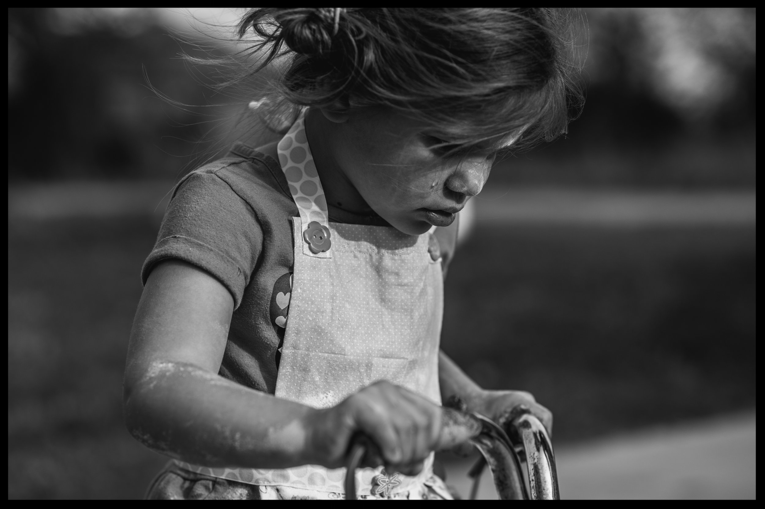 Little girl on a bike crying, black and white