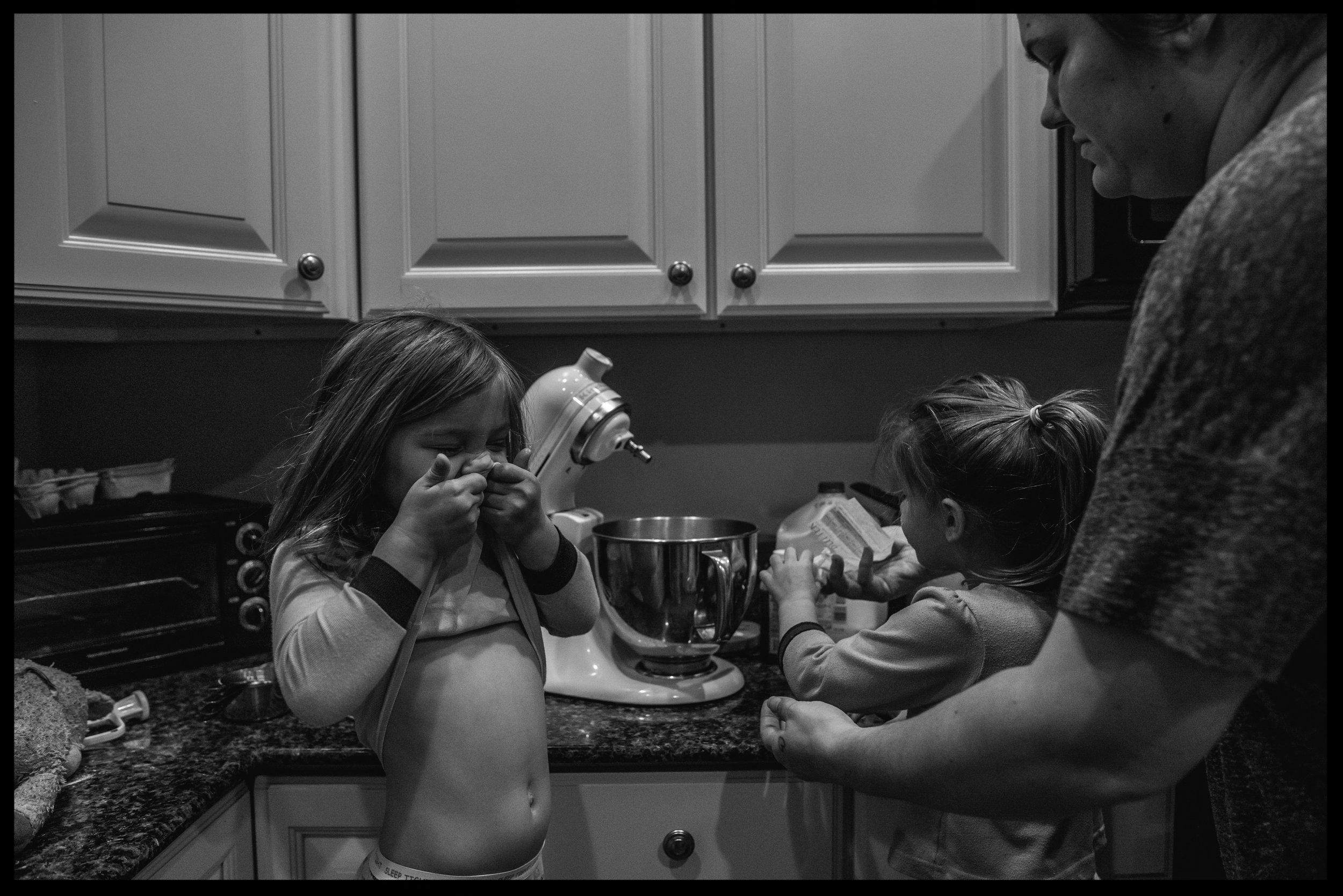 Daughters helping their mother make breakfast, black and white