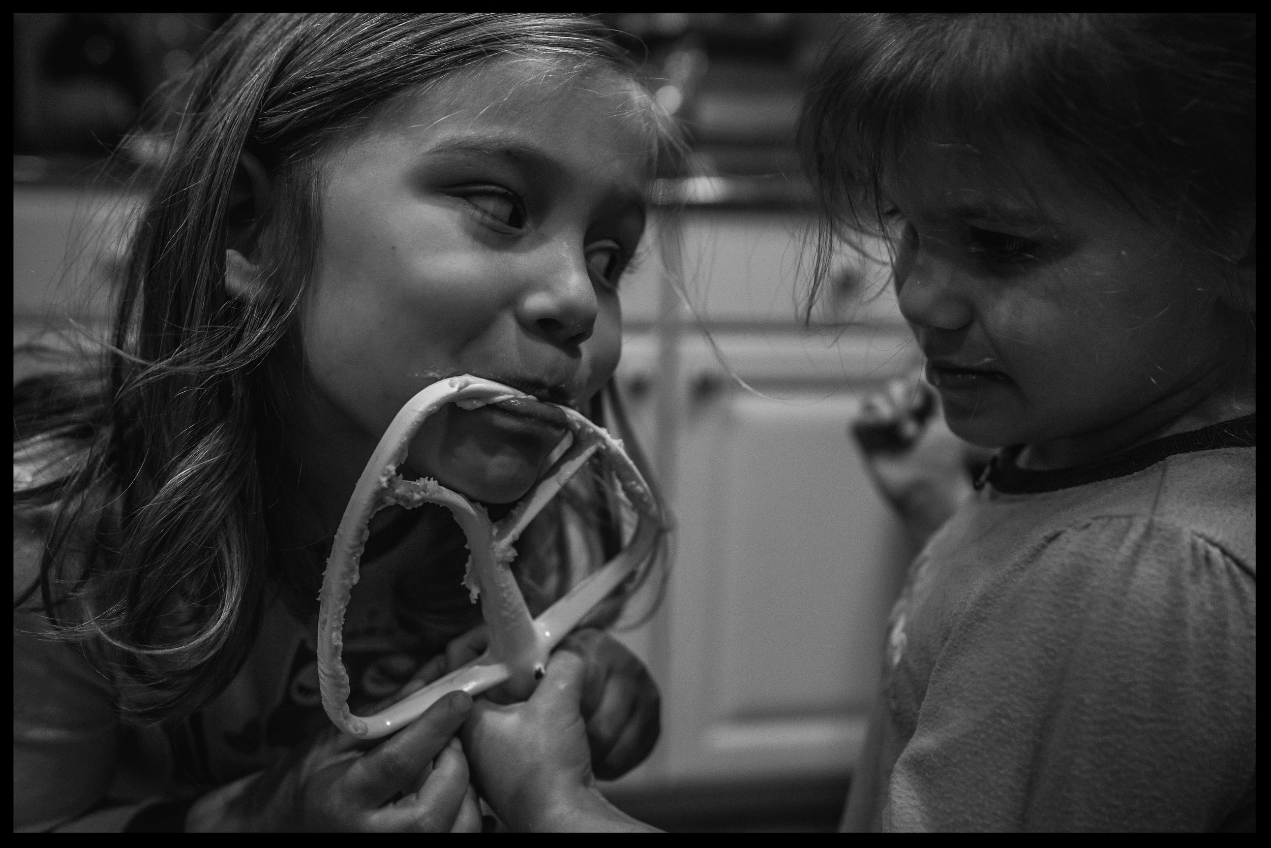 Sisters taking turns licking the beater, black and white
