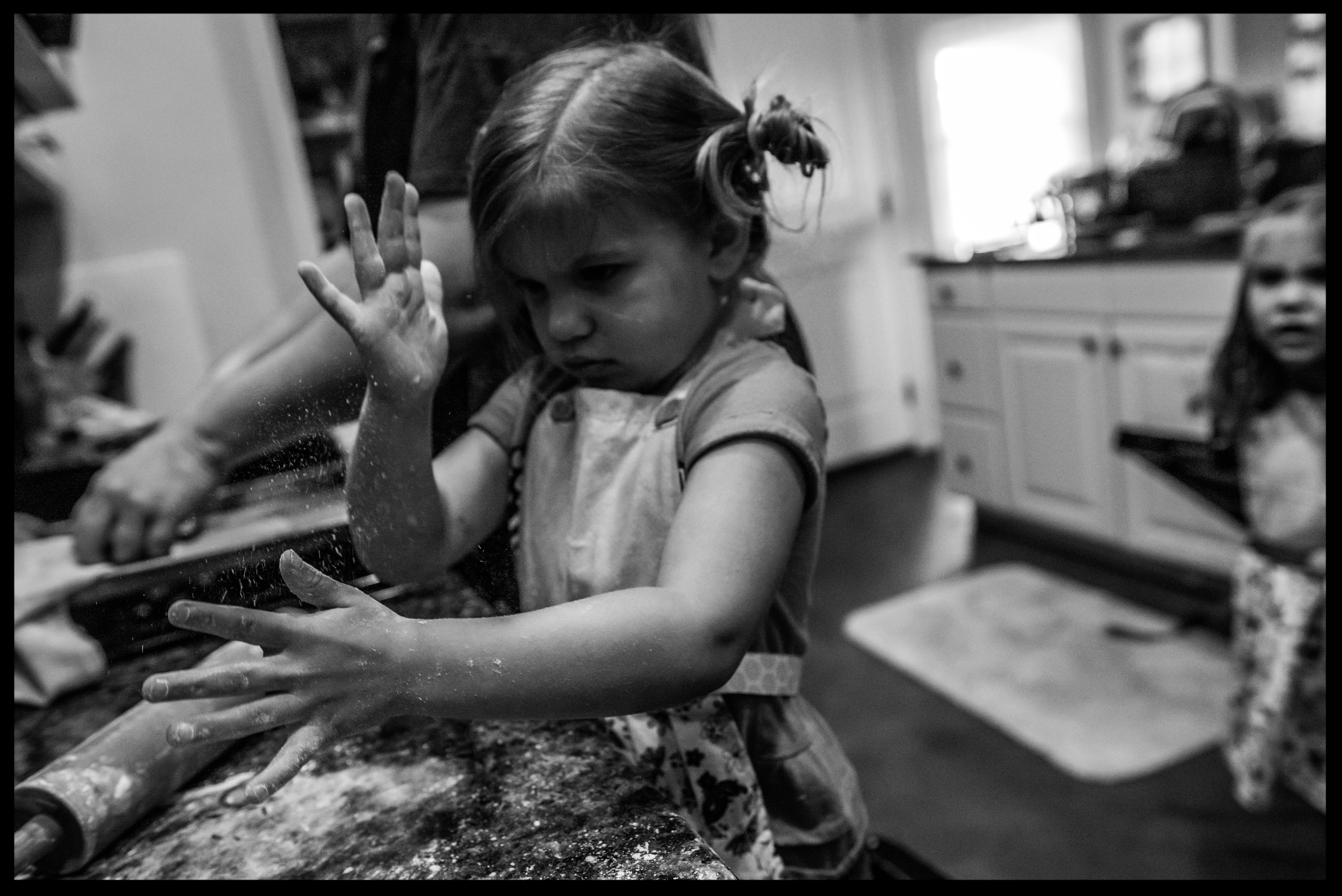 Little girl playing in the flour, black and white