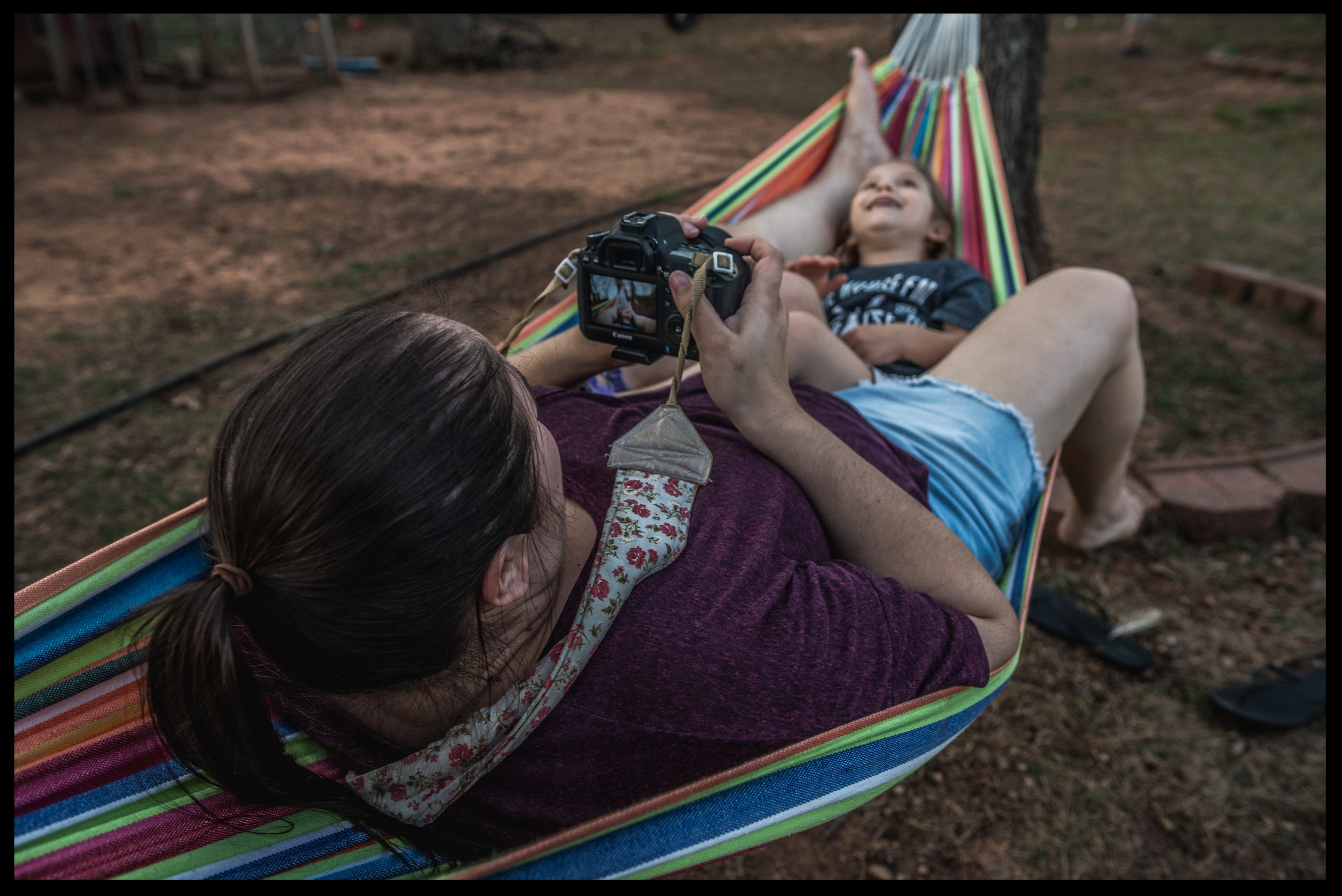 Mother taking a photo of her daughter in a hammock, color