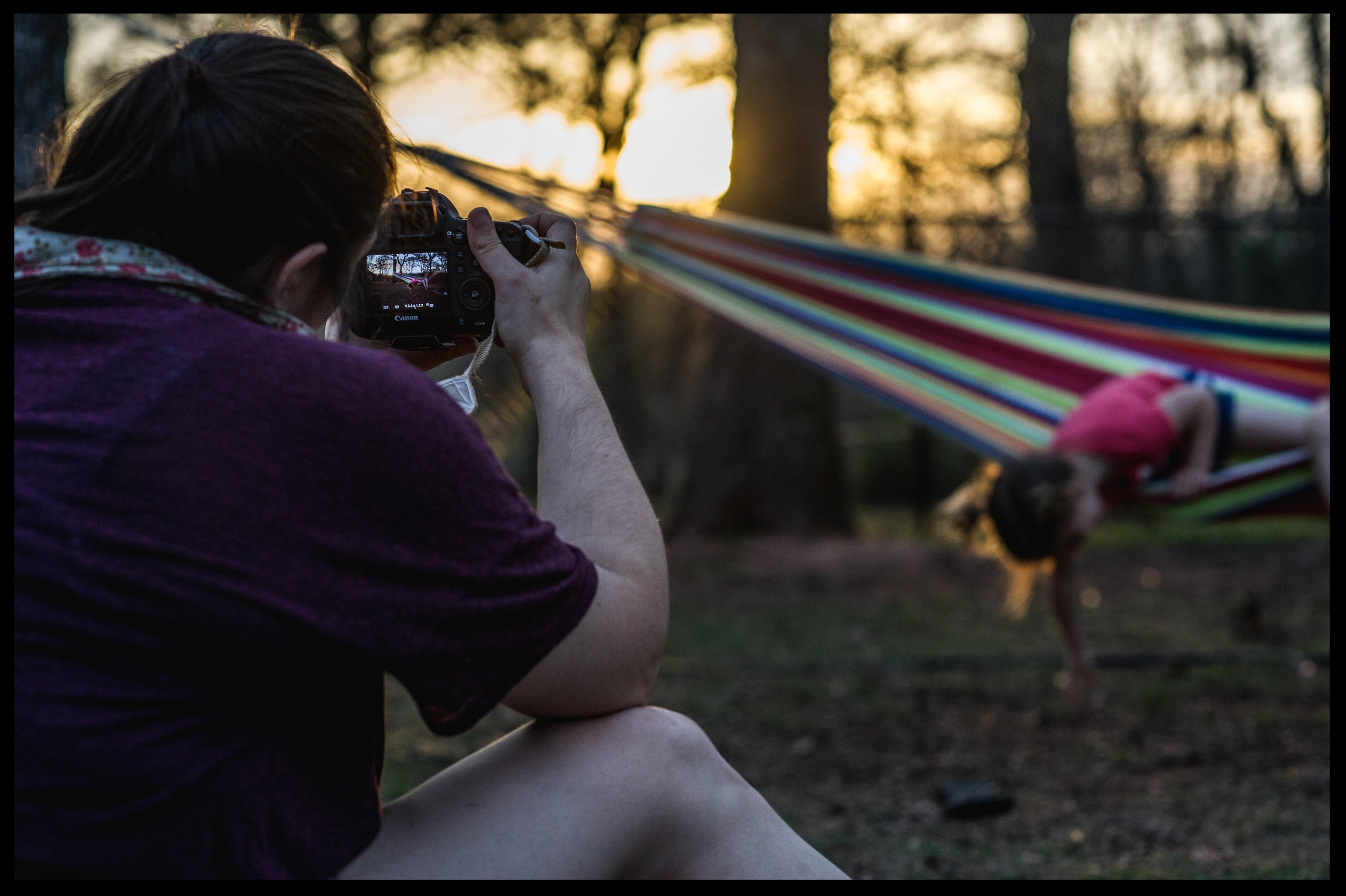 Mommy takes photo of her daughter hanging out of the hammock with backlit hair, color