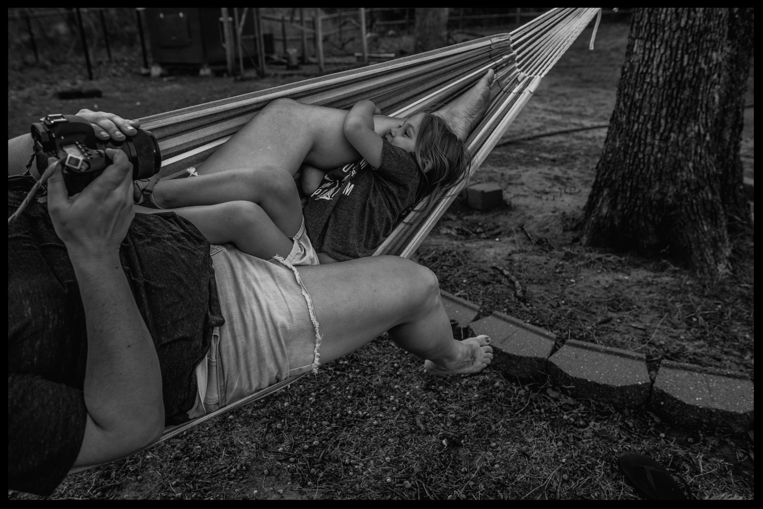 Mom taking a photo of her daughter who is holding onto her leg in the hammock, black and white