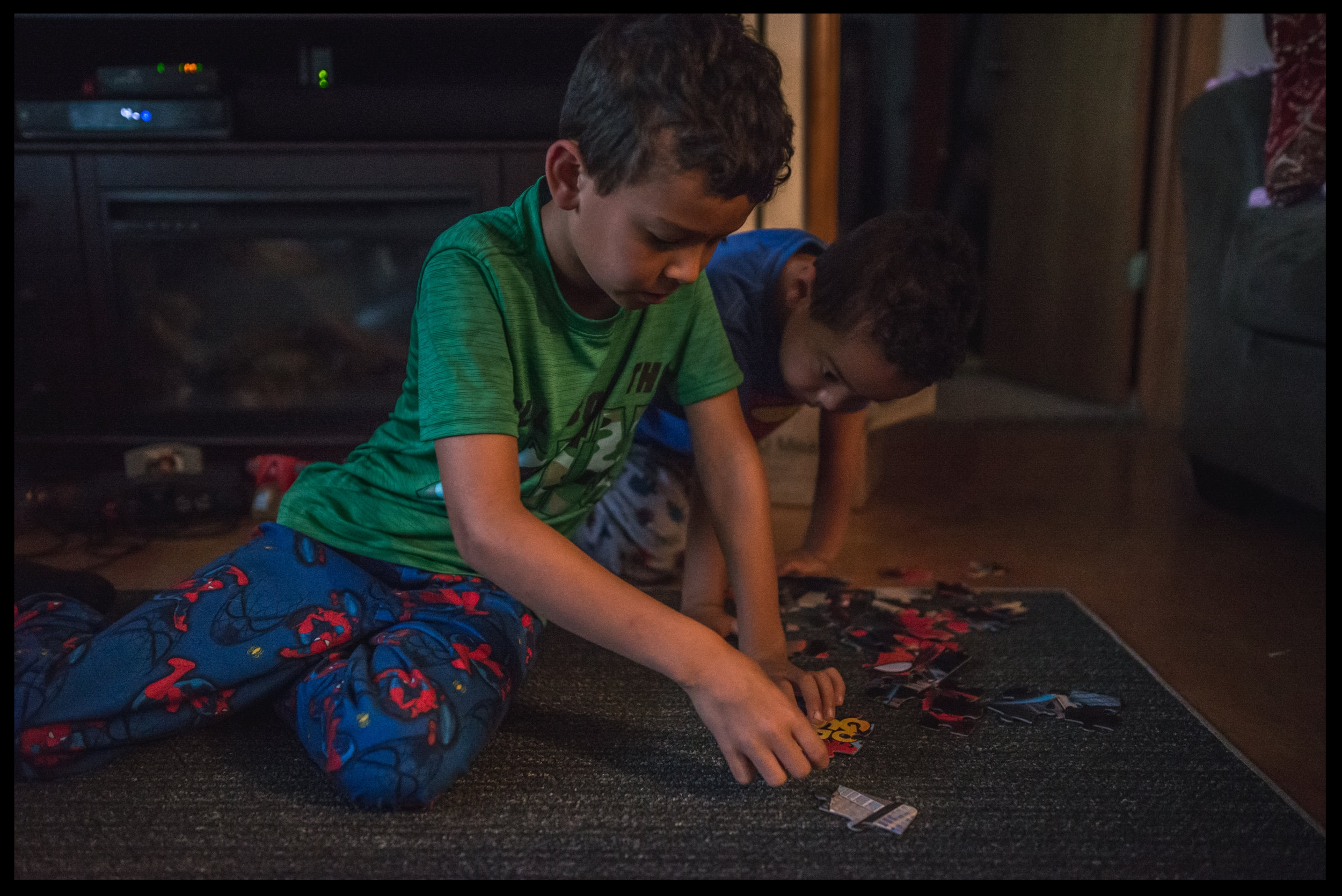 Two boys putting together a puzzle in their pajamas