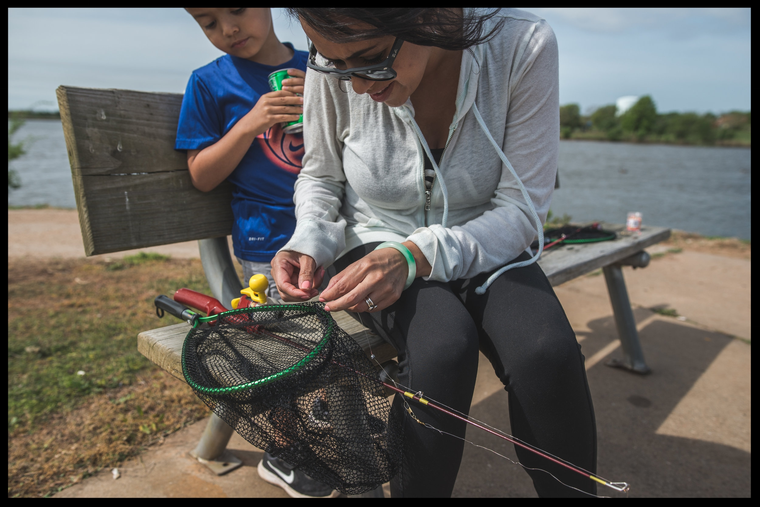 Mother tries to untangle kid's fishhook from a net, color