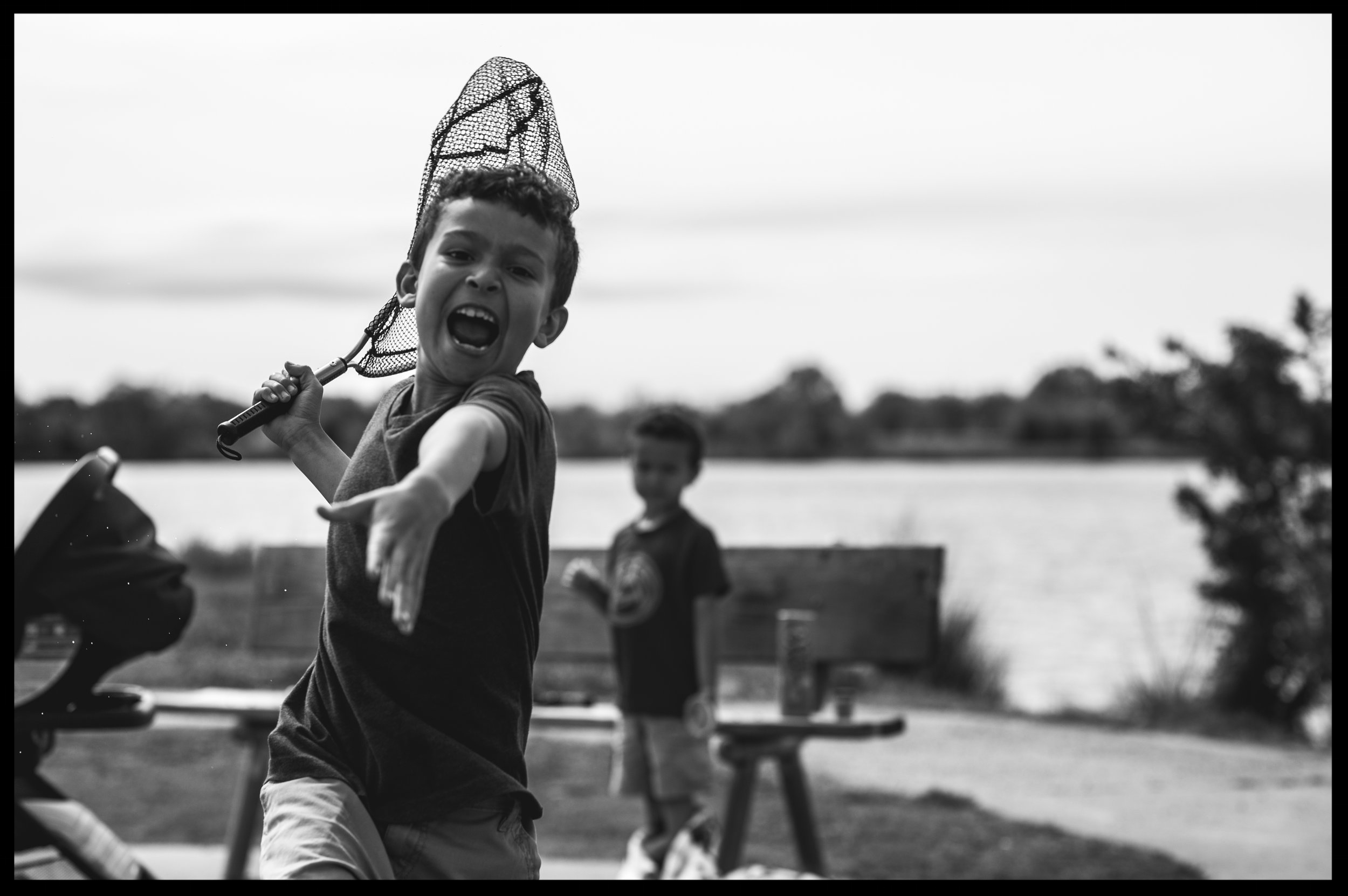 Little boy running toward the camera with a net, black and white