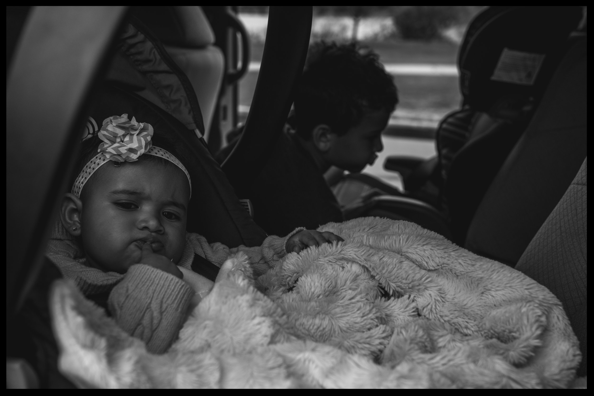 Two kids in the car waiting to go, making cute faces, black and white