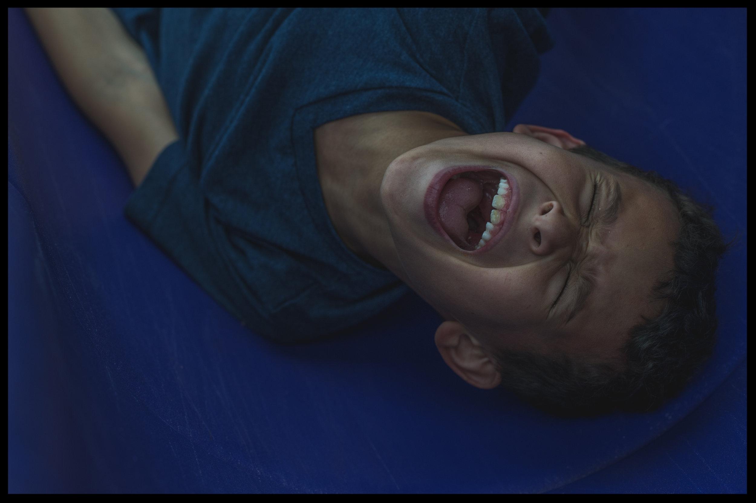 Little boy on a blue slide screaming, color