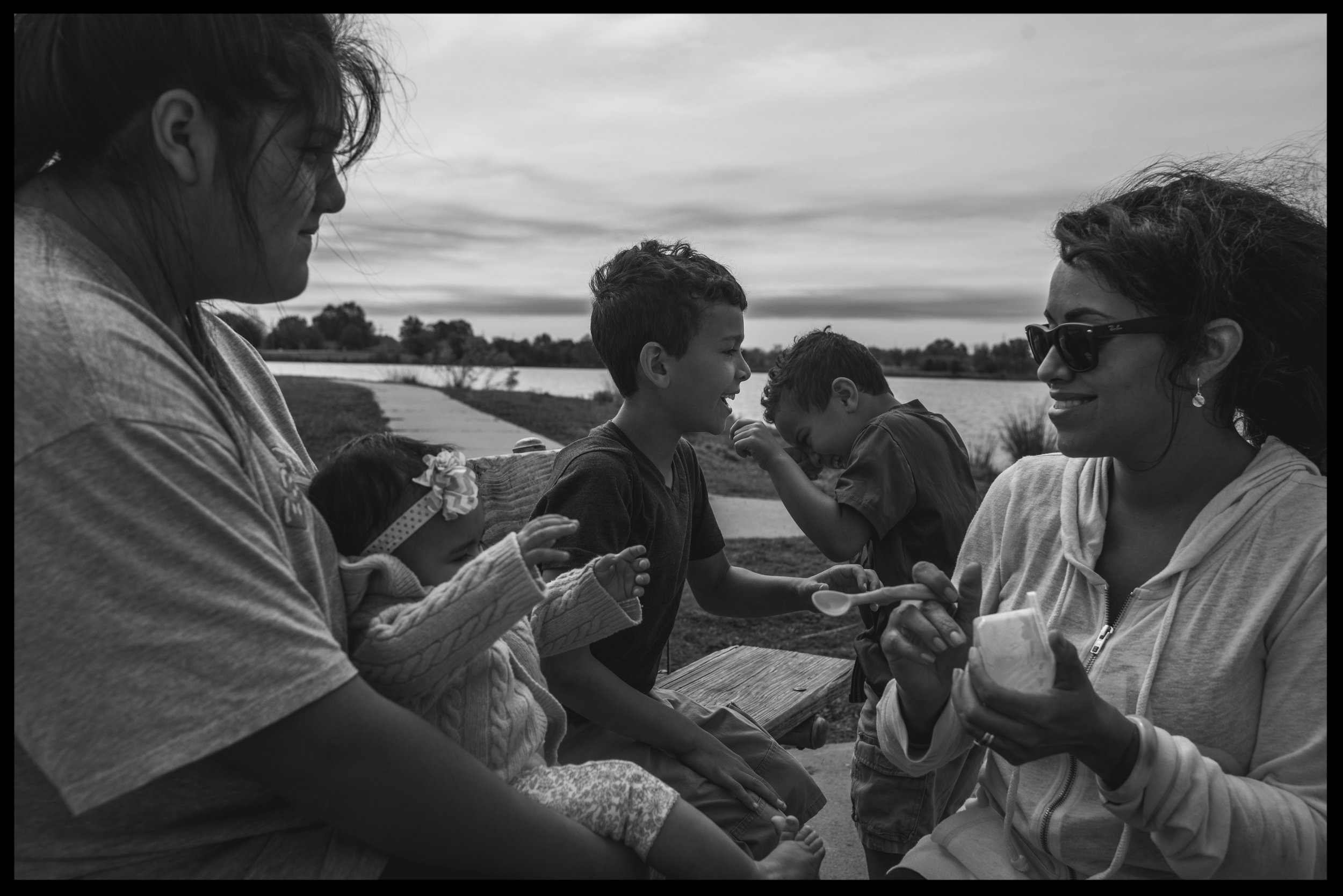 Mom, aunt, and three kids laughing together at the lake, black and white