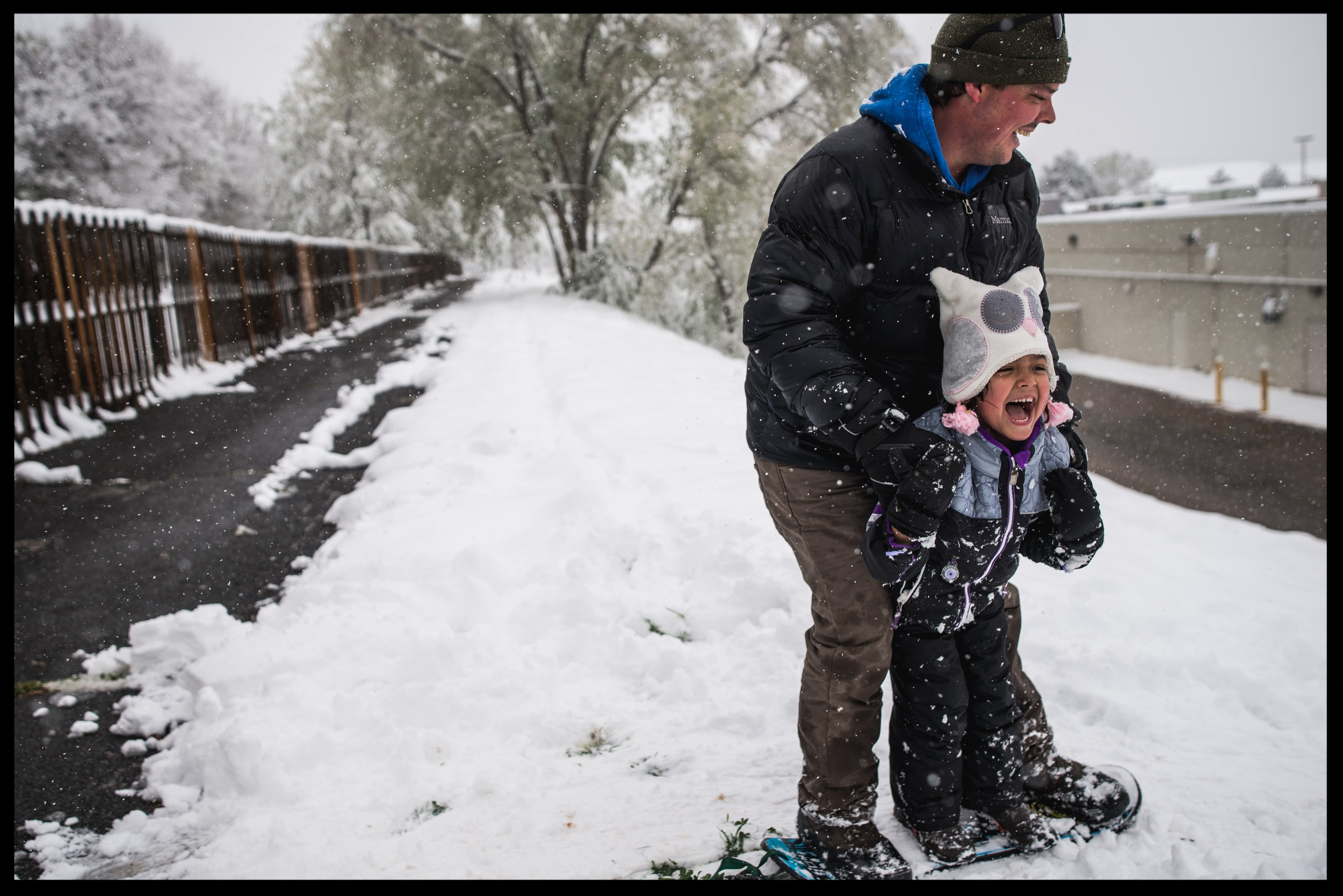 Little girl and her daddy standing on a snowboard, sliding down a hill in the snow, color