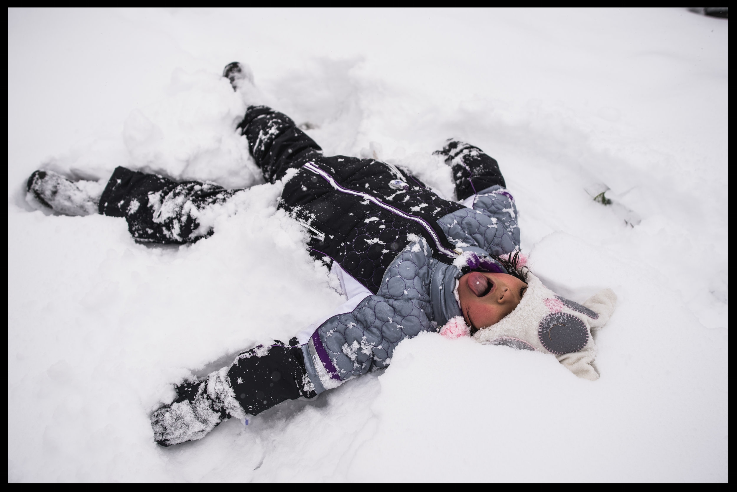 Little girl making a snow angel, snowflake on her tongue, color