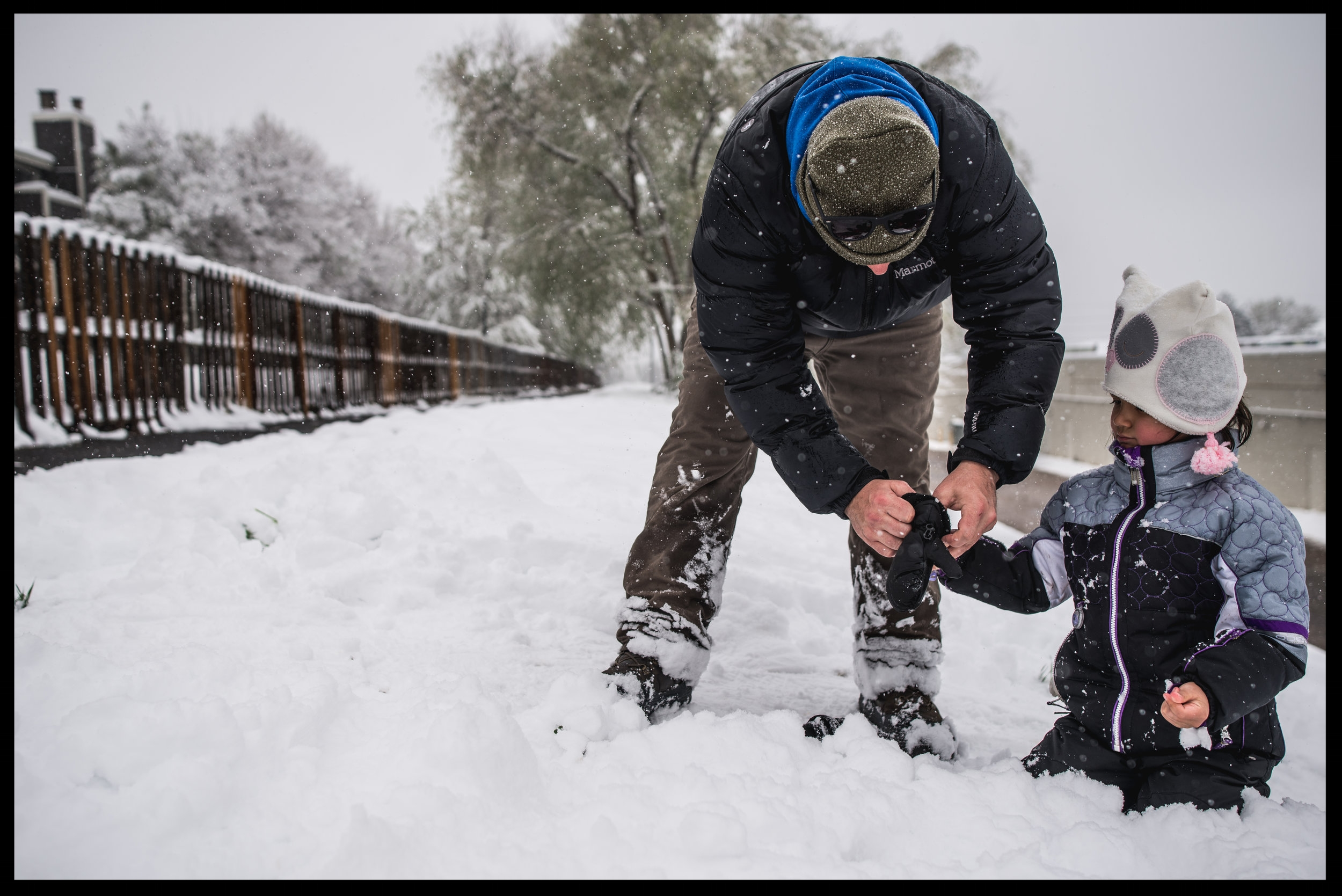 Father helping his daughter put on her winter gloves in the snow