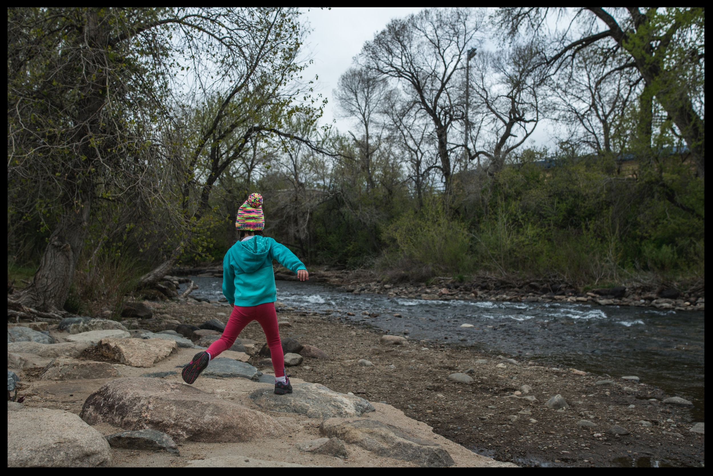 Young girl running on the rocks near a river, color