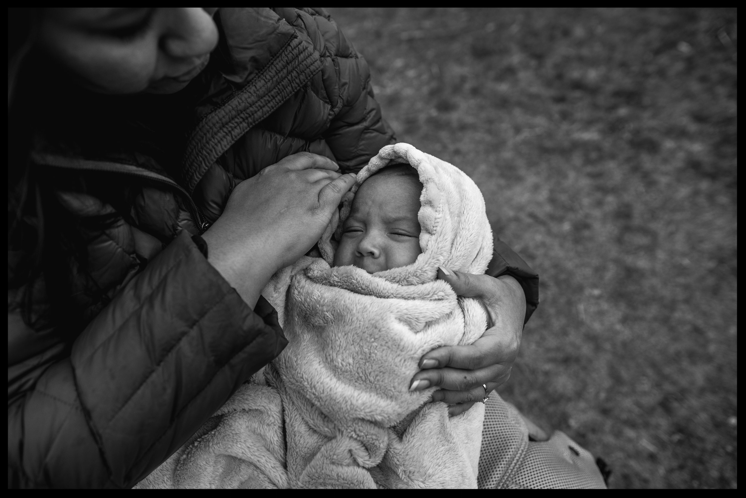 Baby boy bundled up in a blanket with his mother holding him, black and white, Golden, Colorado