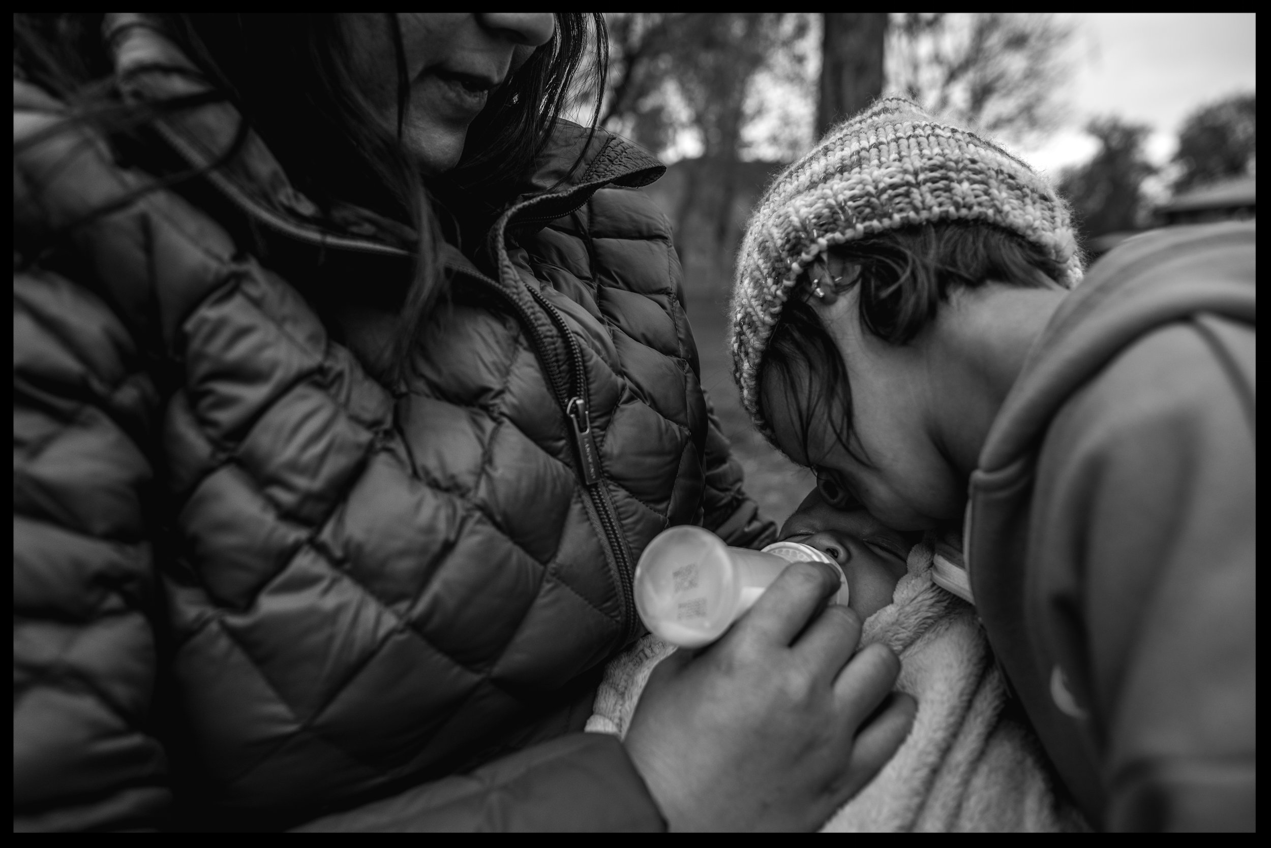 Mother feeding her baby son while his big sister comforts him, black and white, Golden, Colorado