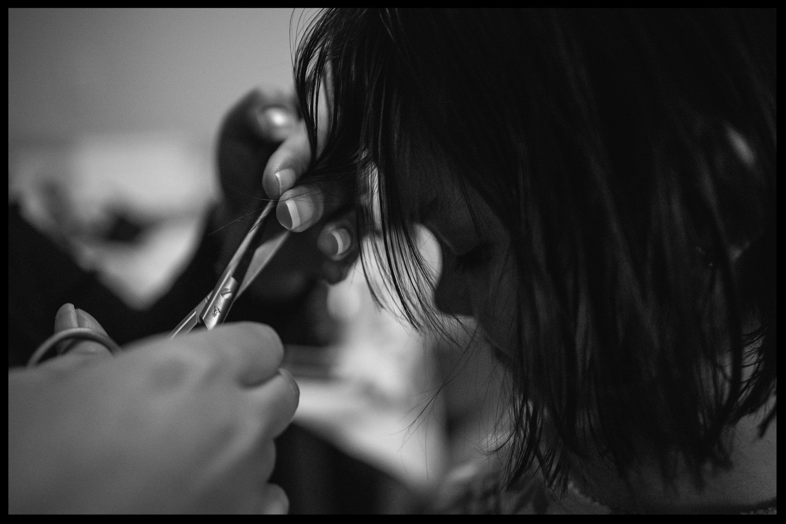 Mother cutting her daughter's hair