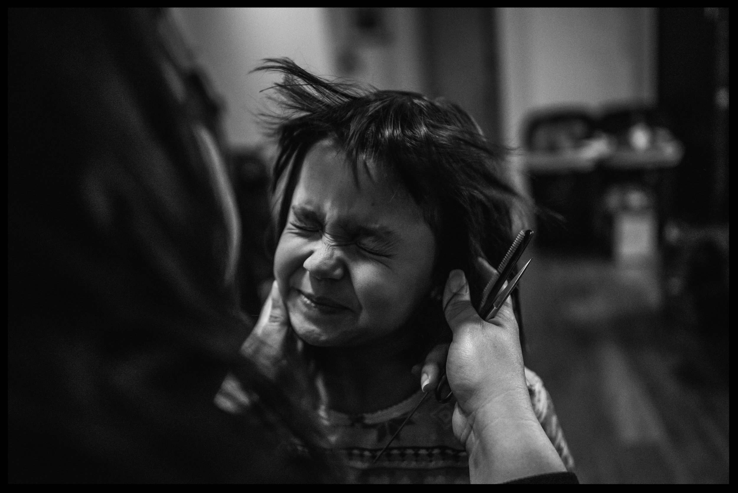 After cutting daughter's hair, she blows the loose hairs off of daughter's face, black and white, Lakewood, Colorado