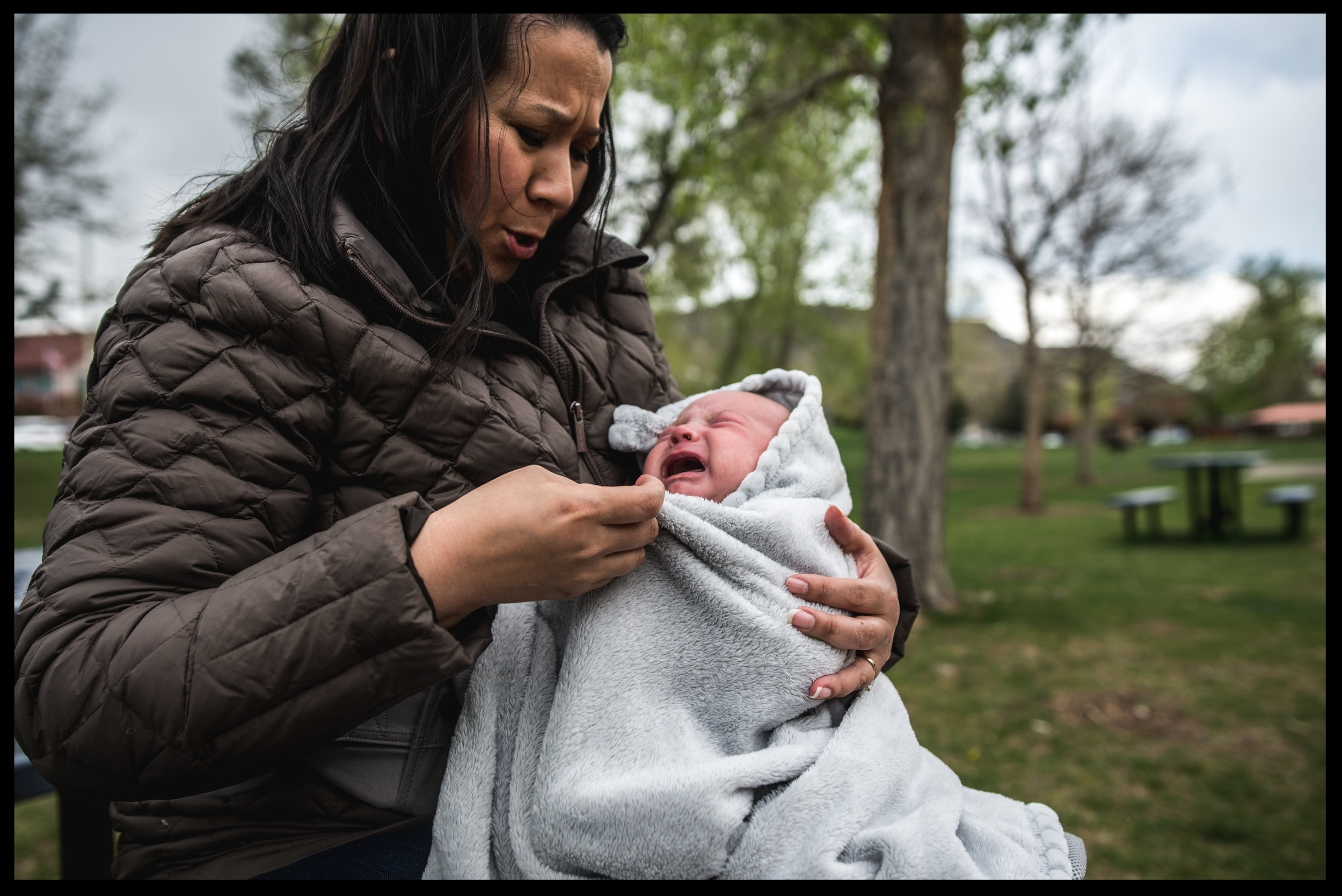 Baby in his mother's arms crying, color, Golden, Colorado