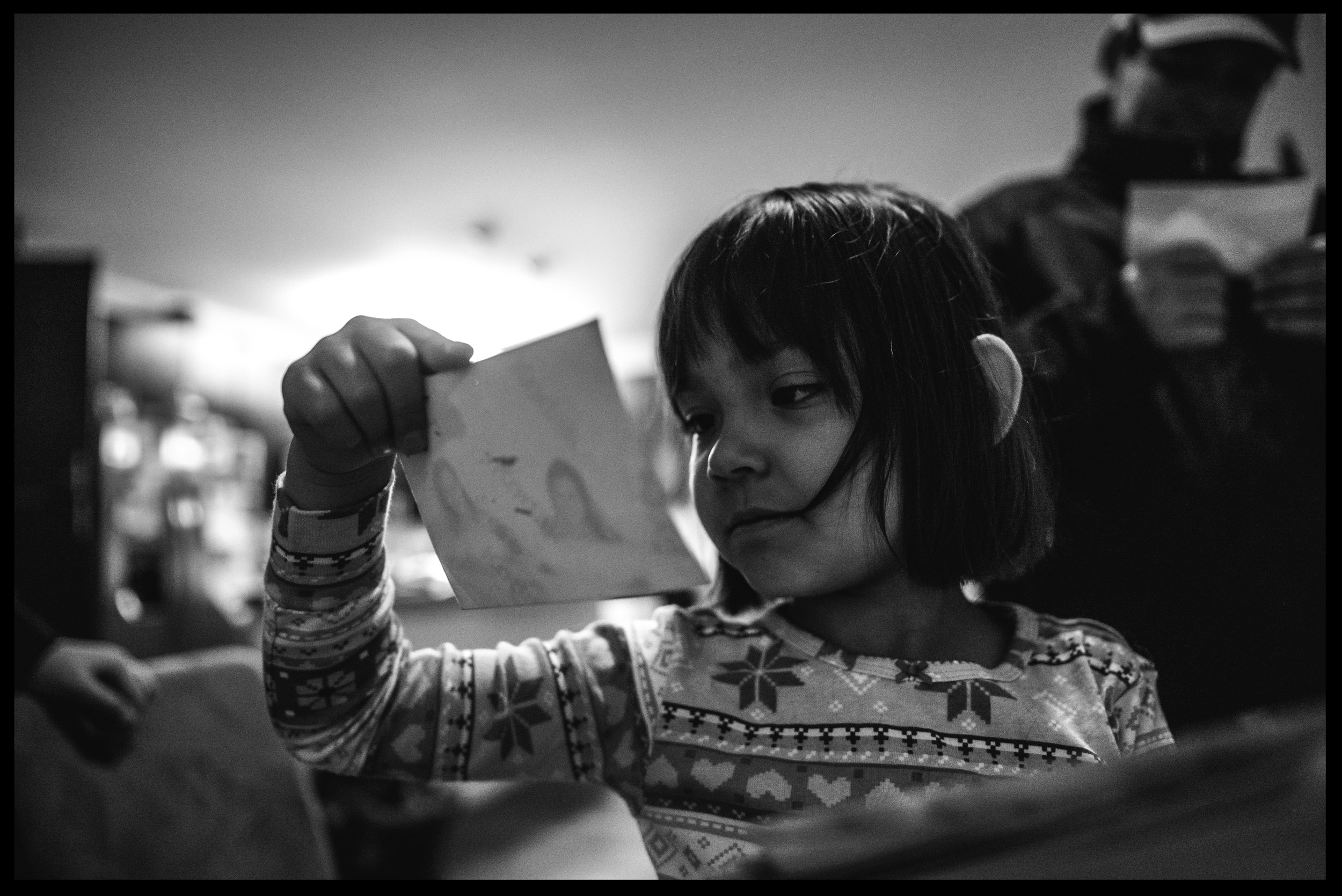 Little girl chewing on her hair and looking at family photos, black and white, Lakewood, Colorado