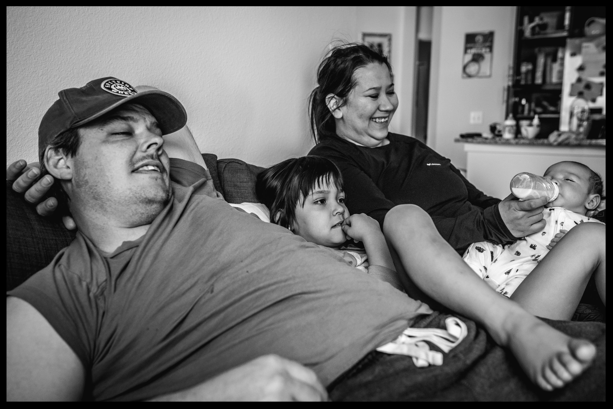 Parents and two kids all cuddling together on the couch, black and white, Lakewood, Colorado