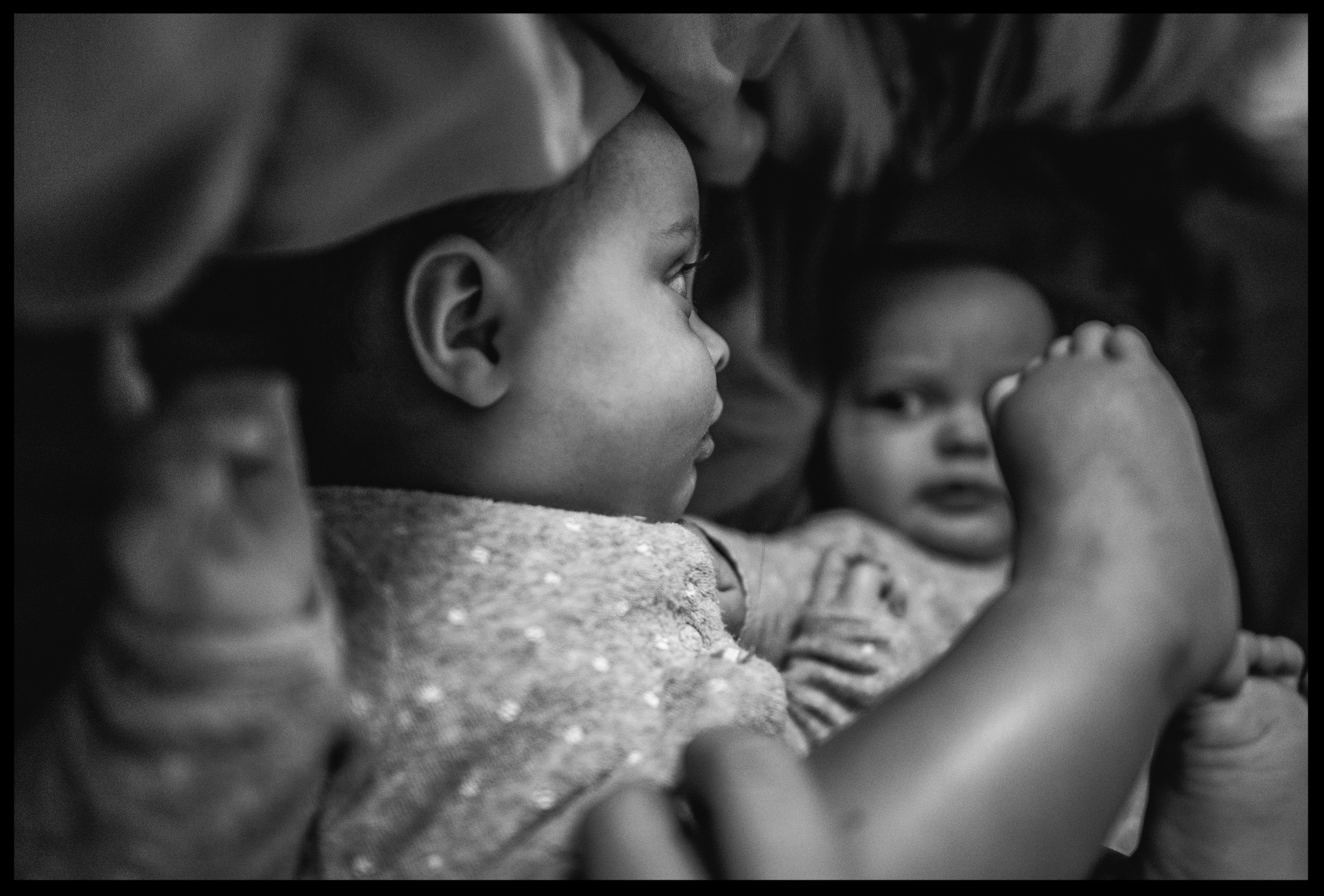 Twin baby girls lying on the bed looking at each other, black and white, Aurora, Colorado