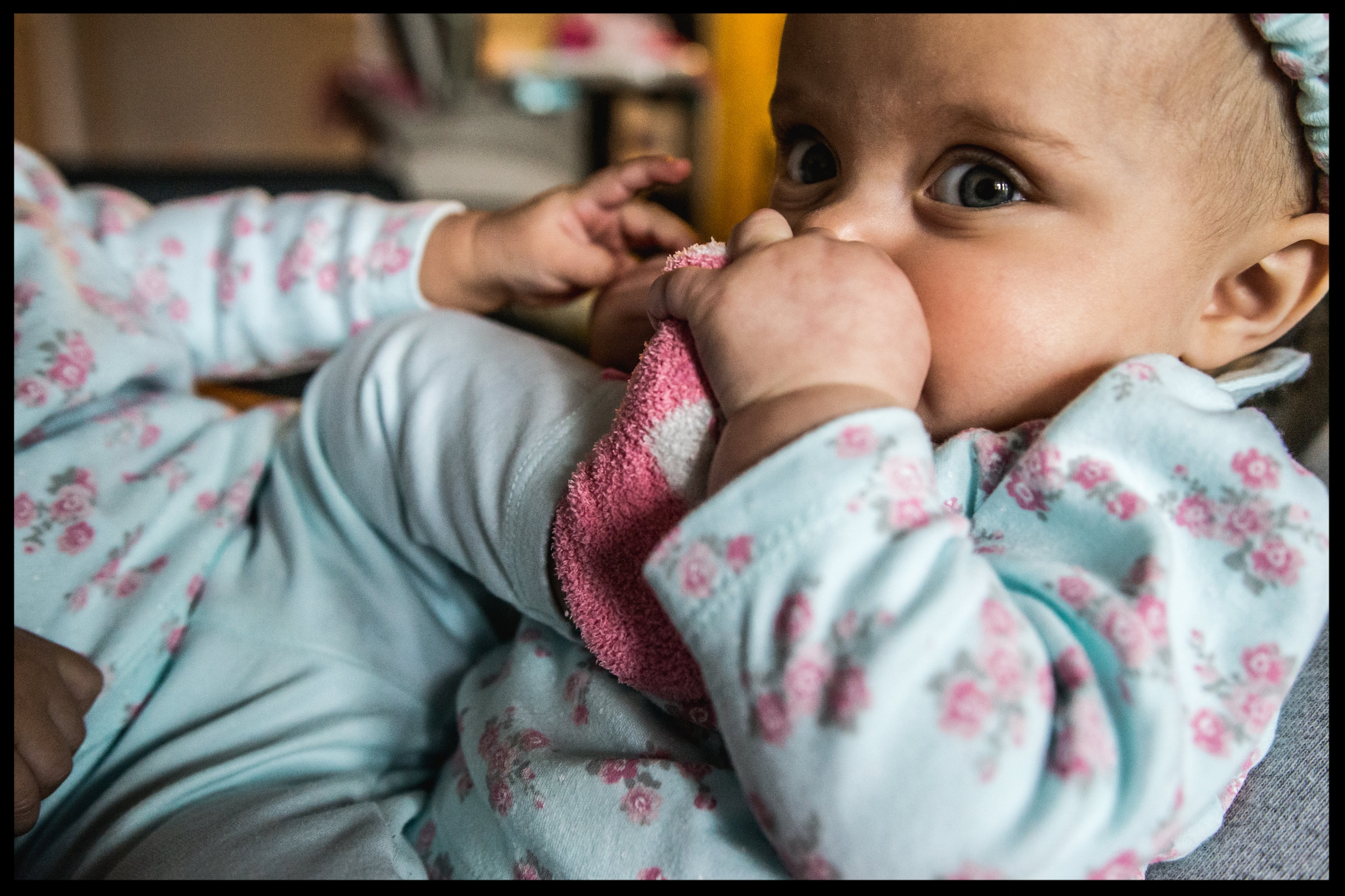Baby girl chewing on her twin sister's foot, color, Aurora, Colorado