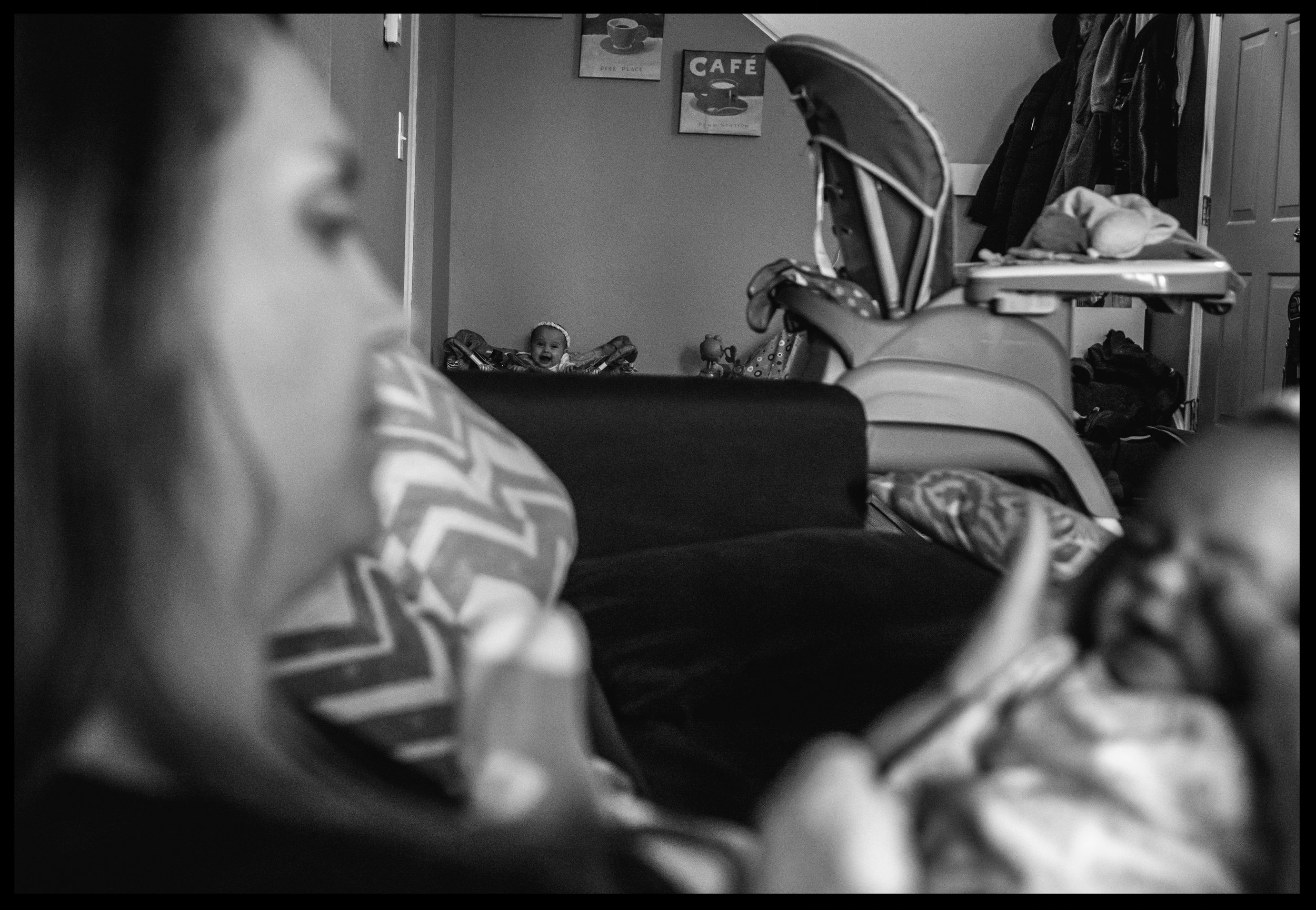 One baby plays in her bouncy toy as her twin sister sits on her mother's lap on the couch, black and white, Aurora, Colorado