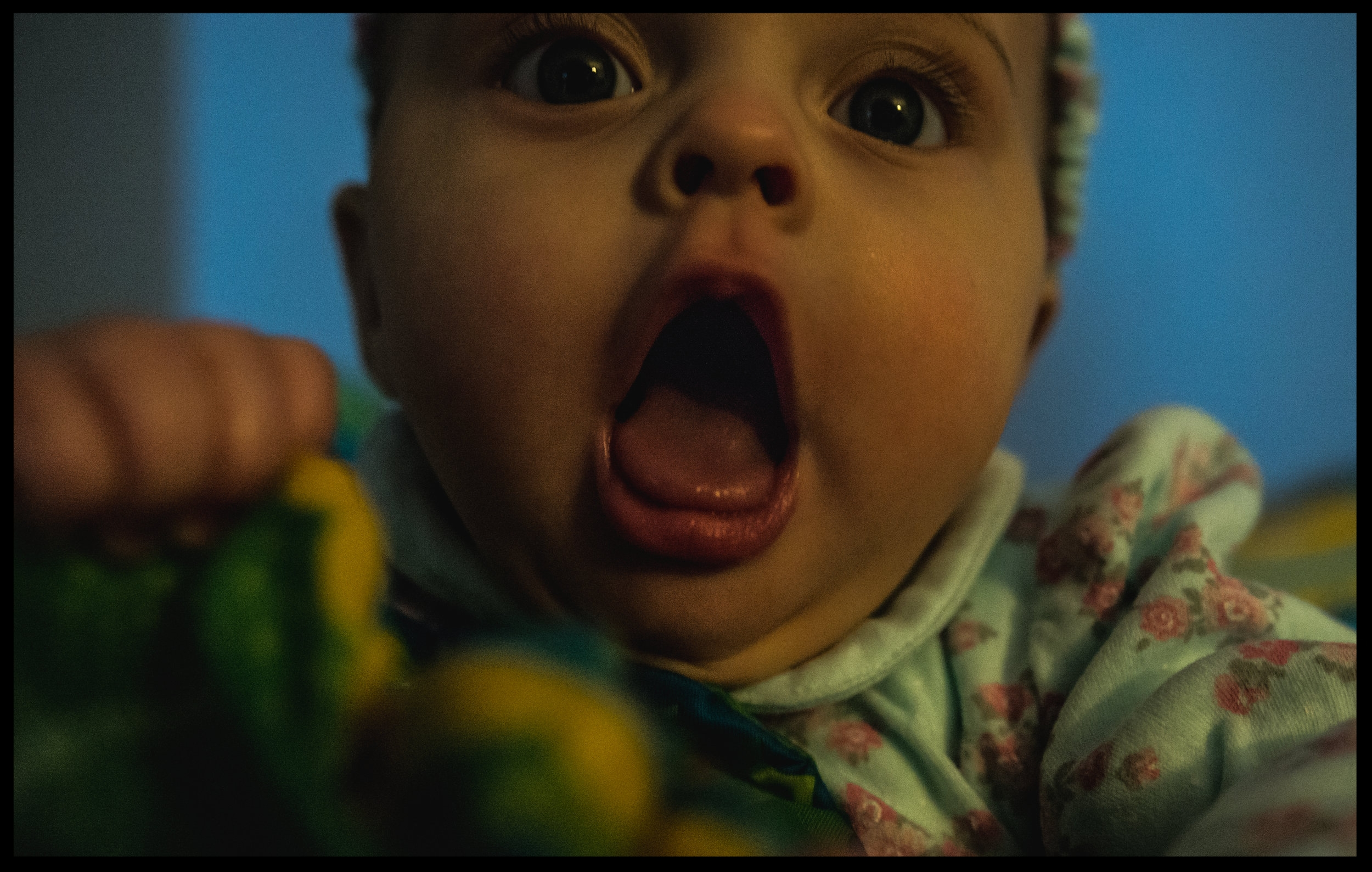 Baby girl with big bright eyes opens her mouth wide, color, Aurora, Colorado