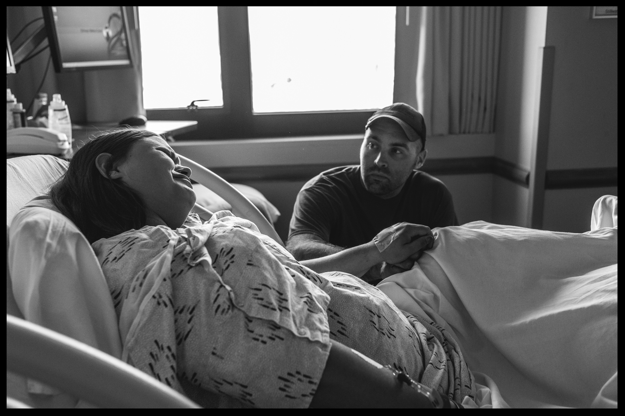 Husband holding the hand of his wife in labor, black and white, Stillwater, OK