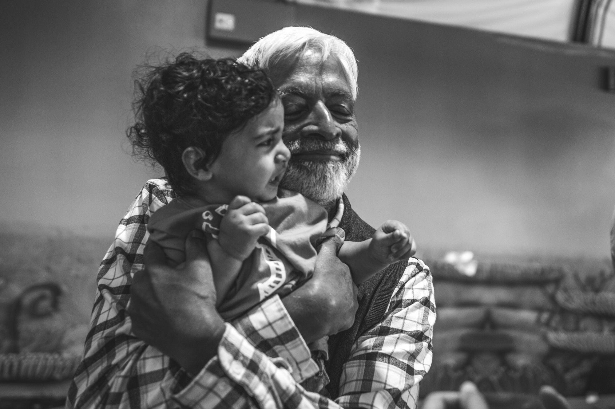 Man hugs one year old boy and smiles wide, black and white