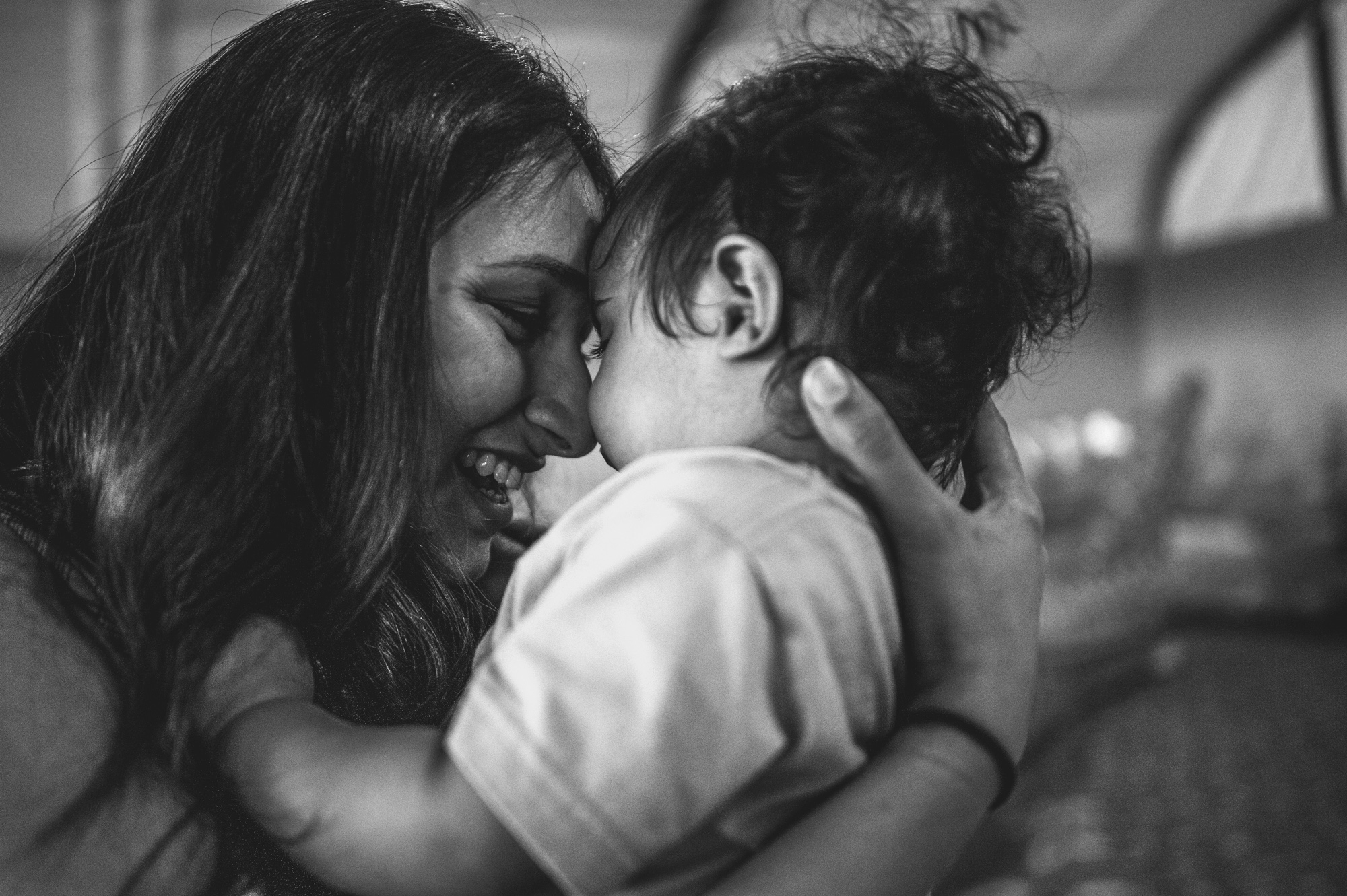 Mother puts her forehead to her baby boy's head on his one year birthday, black and white