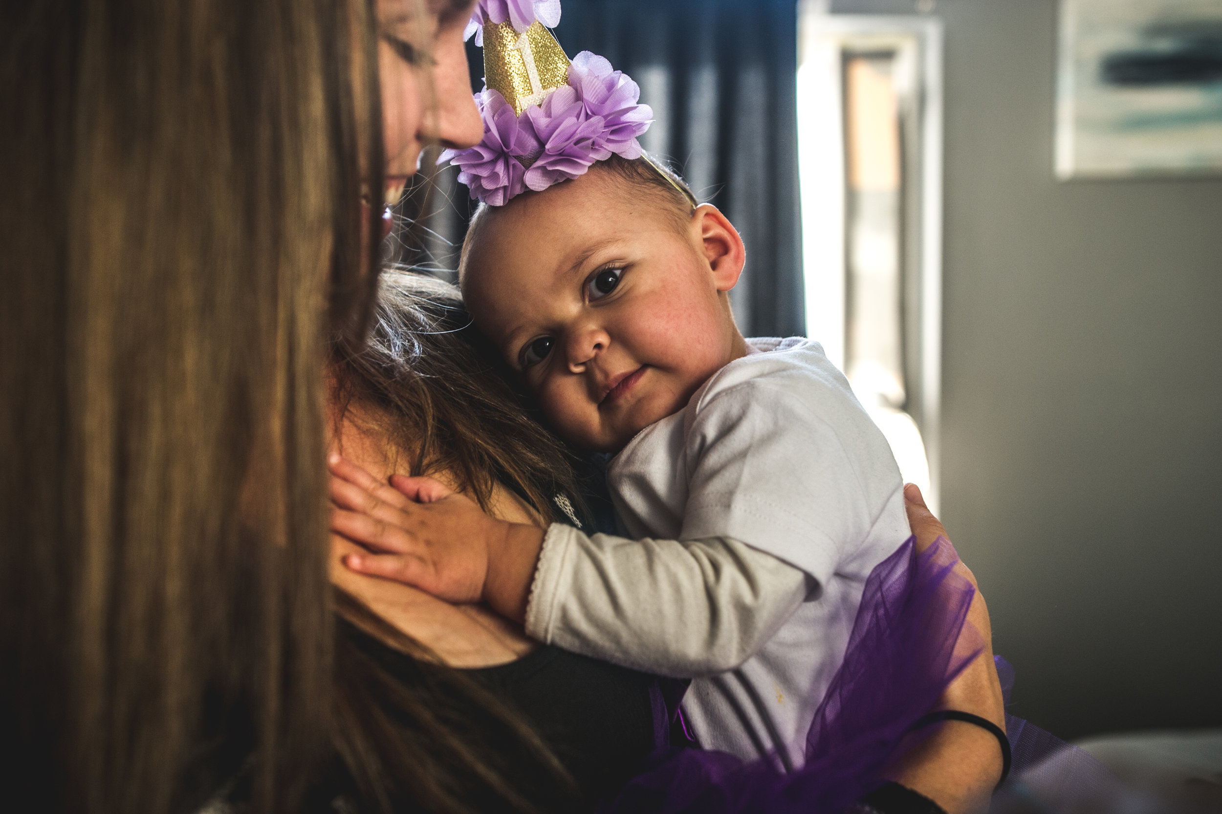 One year old girl wearing a purple tutu and party hat cuddling up to her mommy, Aurora, Colorado