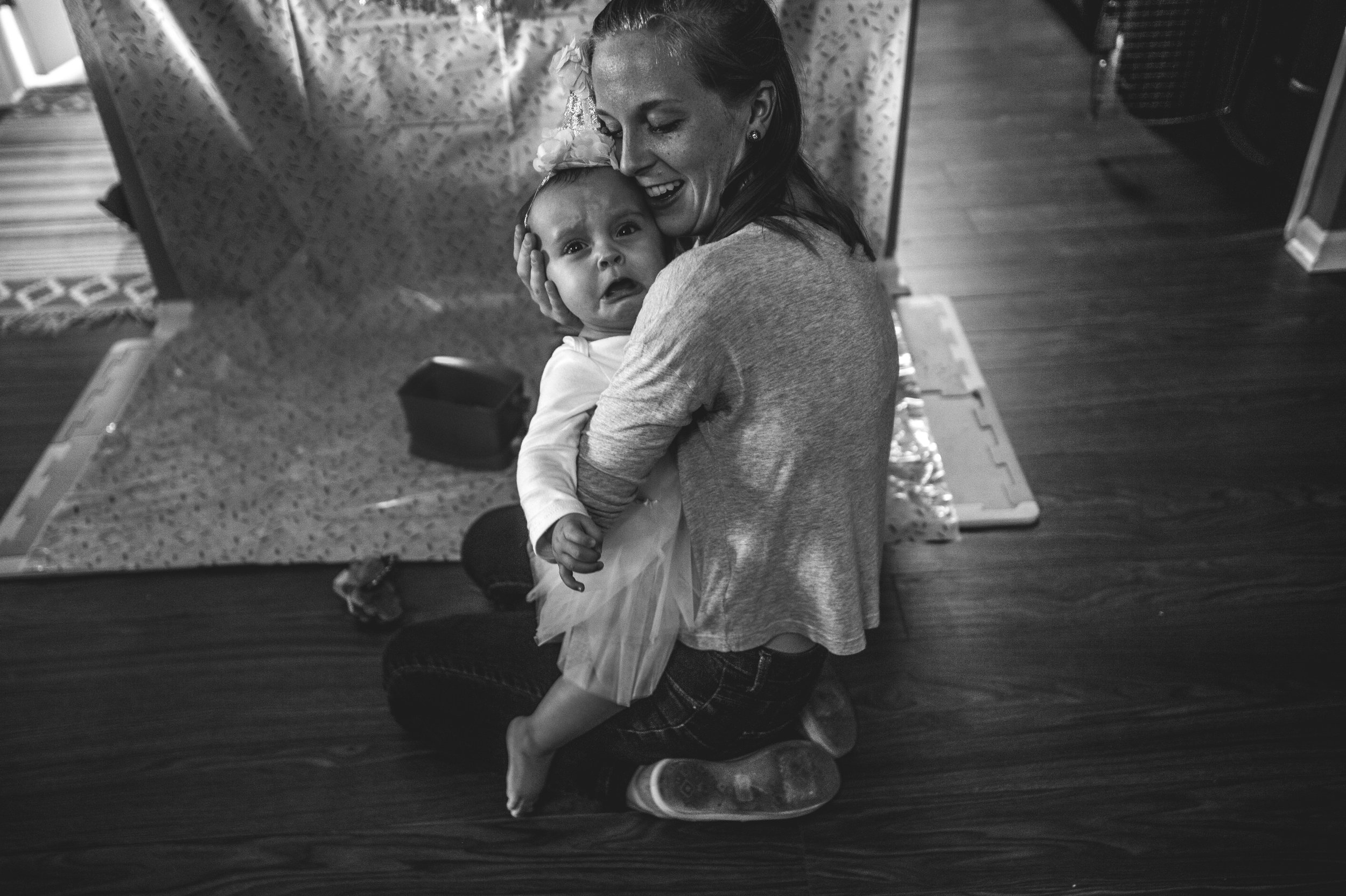 Little girl wearing a tutu and party hat crying in a woman's arms as the woman smiles down on her, black and white, Aurora, Colorado