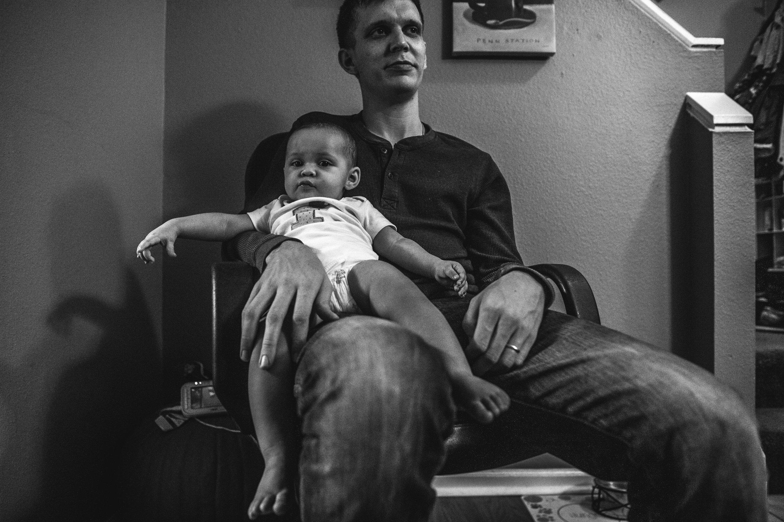 One year old baby girl lying back on her uncle's lap, black and white, Aurora, CO