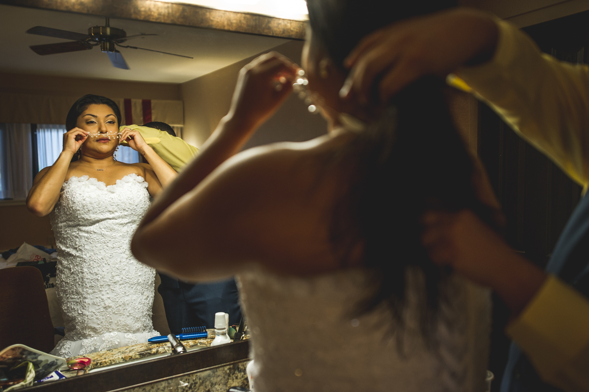 Groom helps his bride put on her head piece as the bride looks in the mirror, Estes Park, Colorado, color