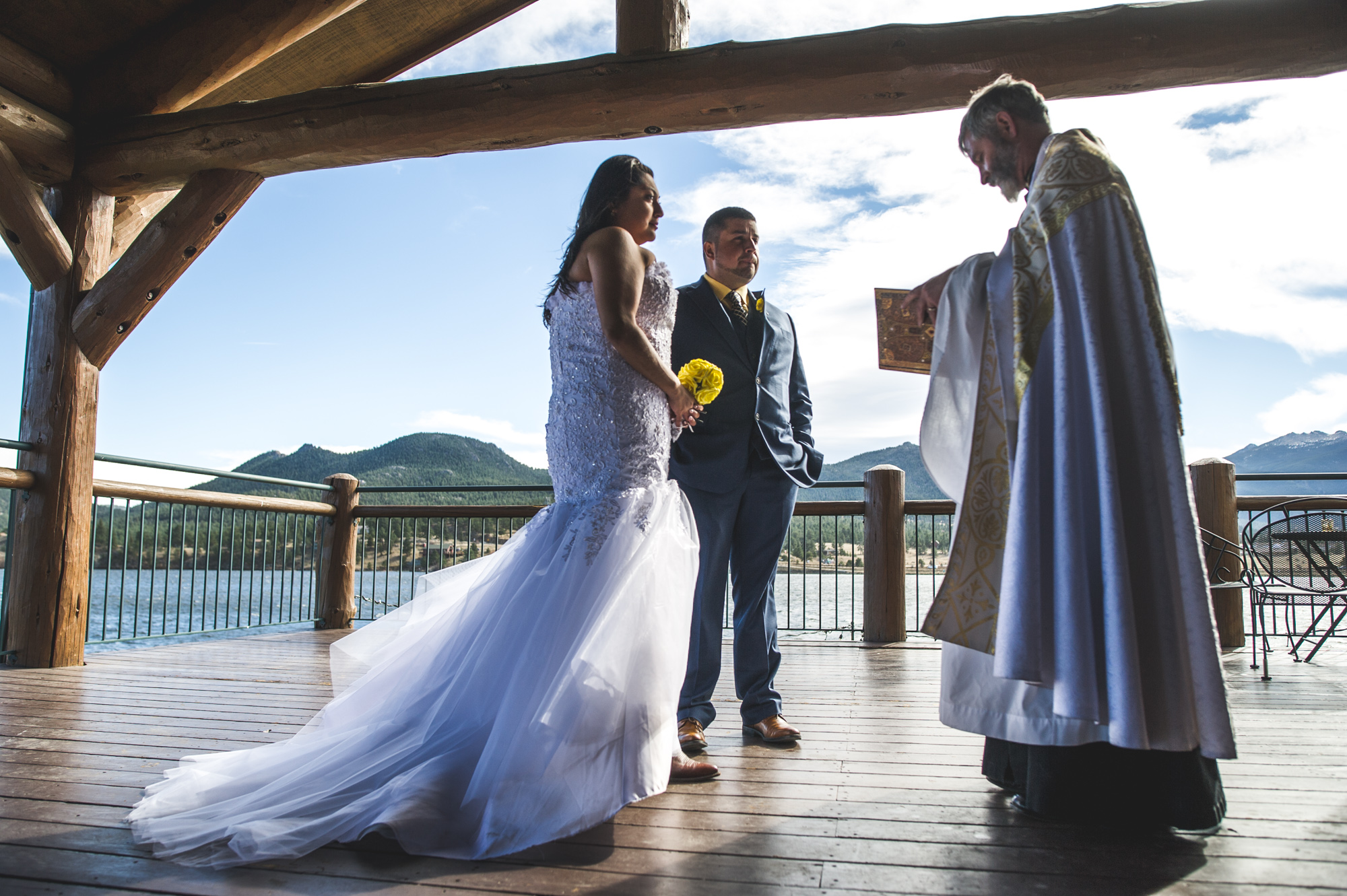 Bride and groom stand on a patio during their wedding ceremony at a resort in Estes Park, Colorado, color
