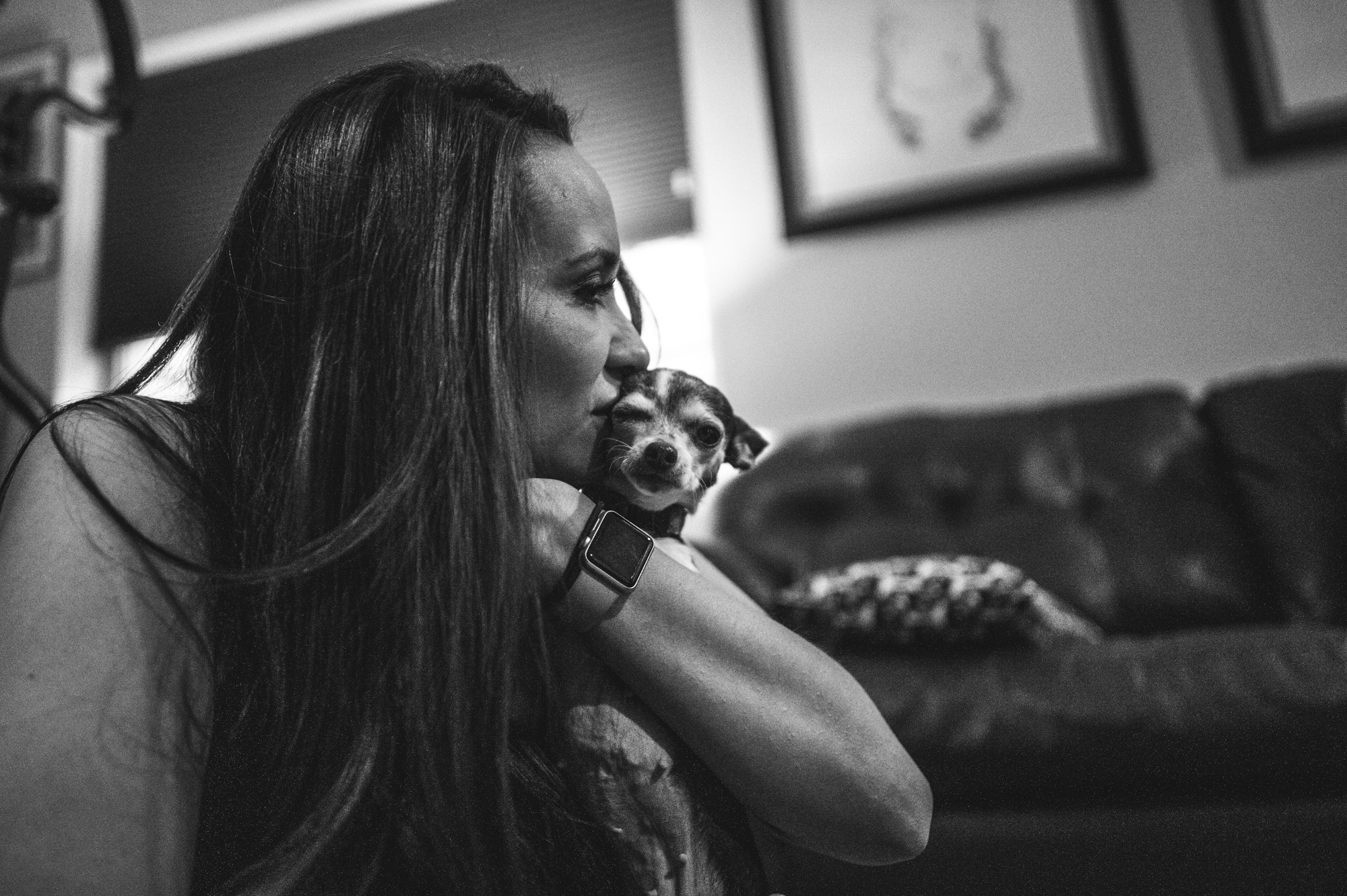 Woman kissing her chihuahua's face as the little dog makes a funny face, black and white, Denver, Colorado