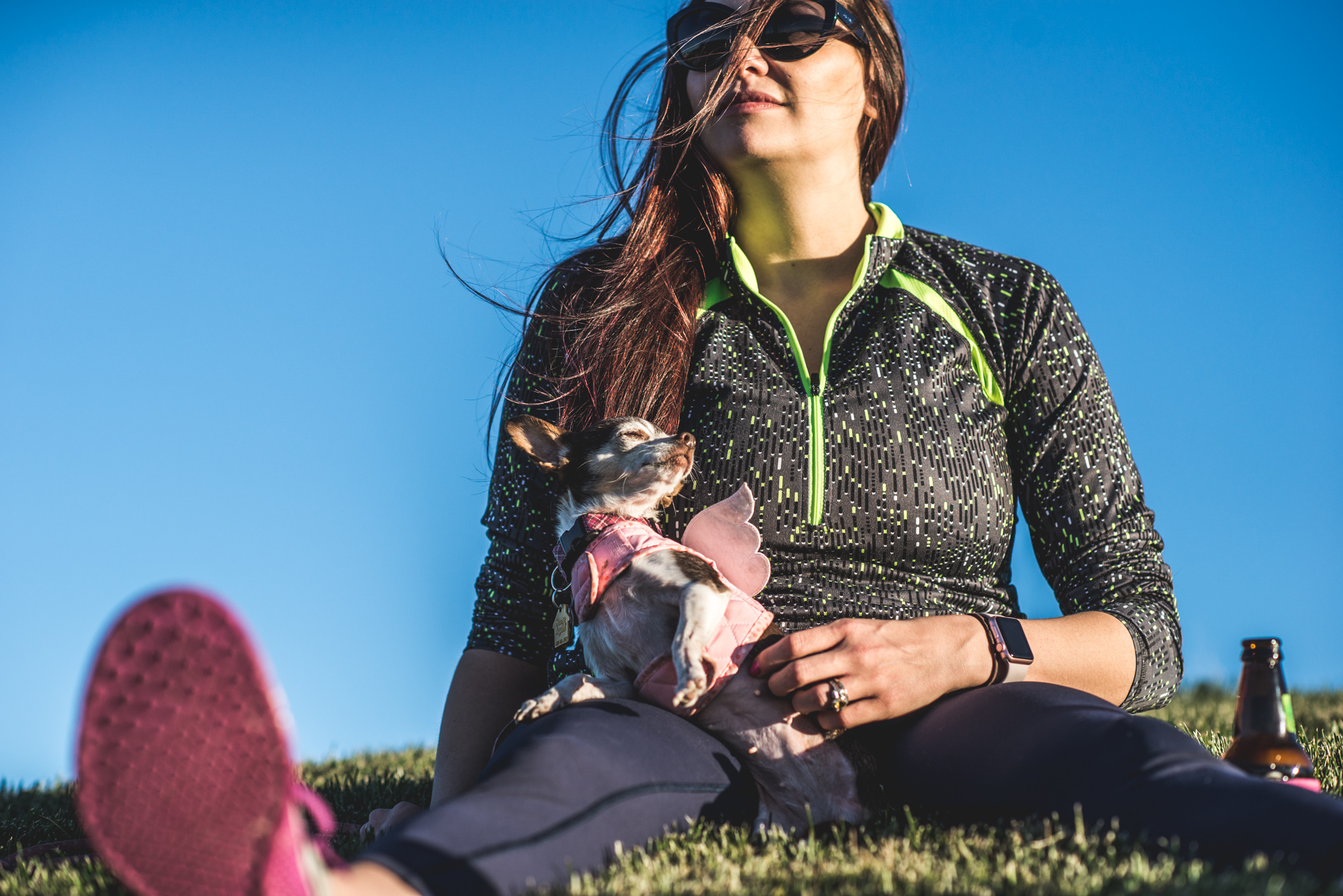 Little dog sits on her owner's lap and closes her eyes as she points her head toward the sun, color, Stapleton, CO